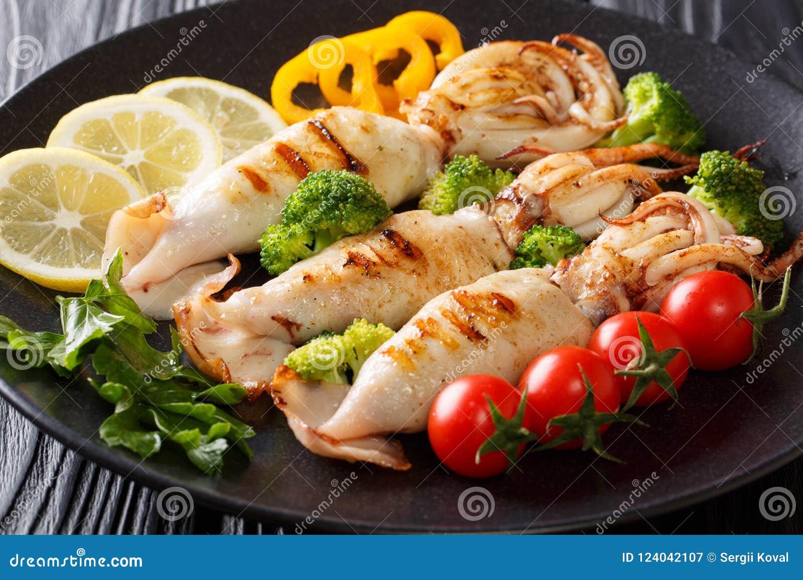 Il calamaro arrostito con i tentacoli è servito con gli ortaggi freschi vicini