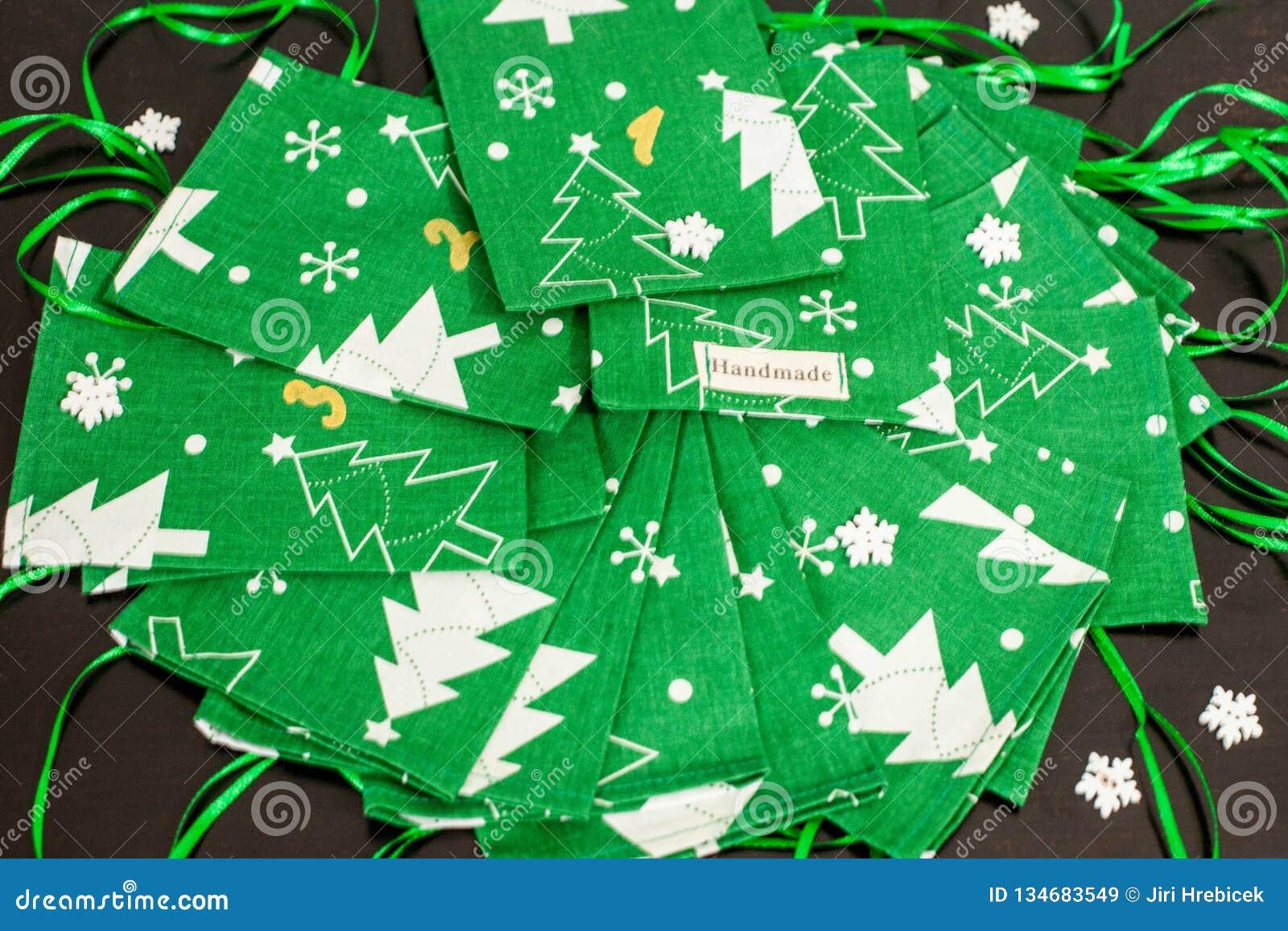 Il calendario fatto a mano di arrivo di Natale per i bambini, arrivo verde ha numerato i sacchi pronti ad essere riempitoe con i