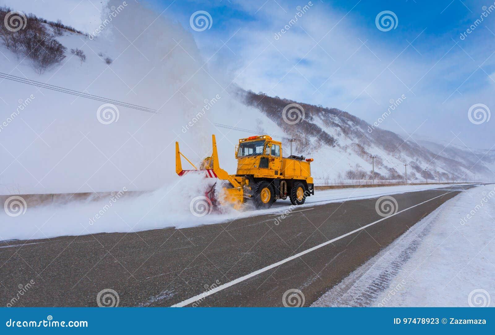Il camion di rimozione di neve del camion dello spazzaneve sta rimuovendo la neve dalla strada principale durante il giorno di in