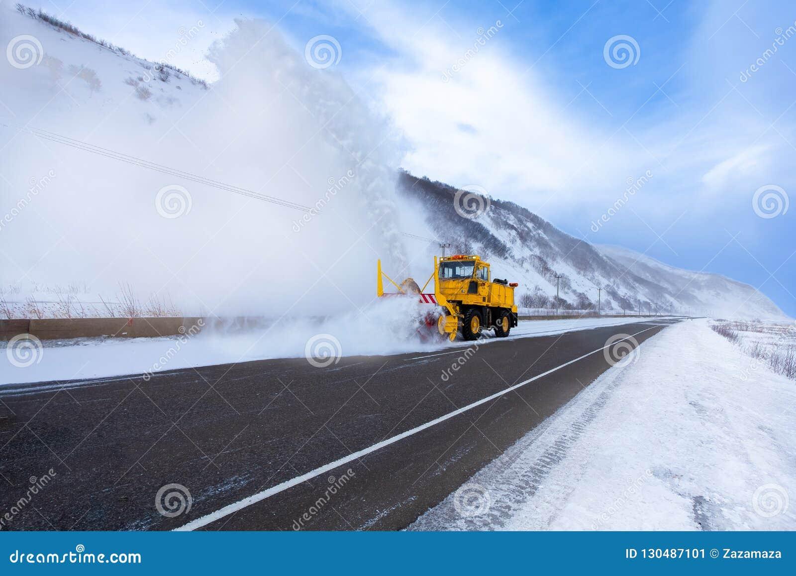 Il camion giallo dello spazzaneve o il camion di rimozione di neve con la lama dello spazzaneve sta rimuovendo la neve dalla stra