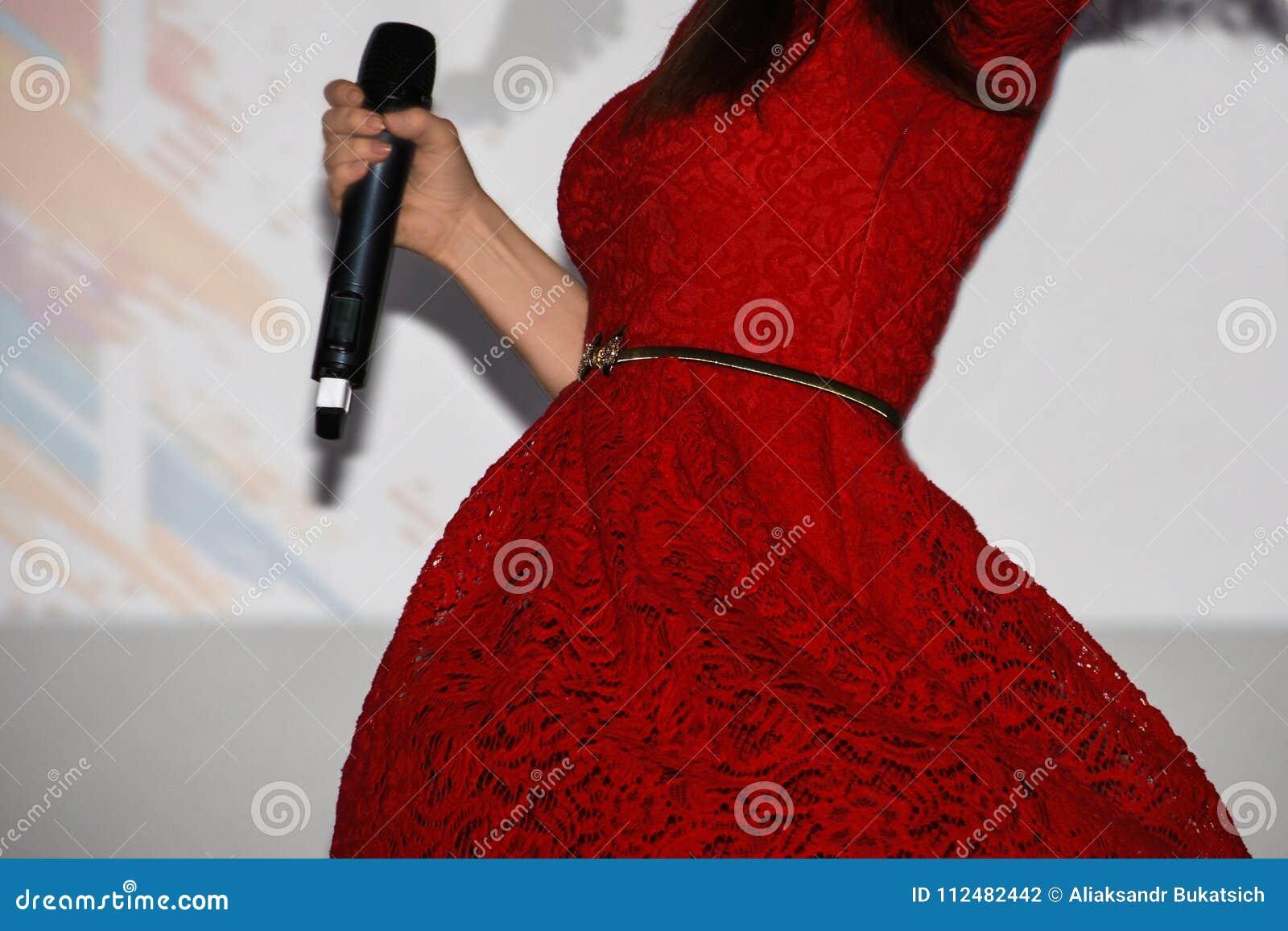Il cantante della ragazza in un vestito rosso luminoso tiene un microfono in sua mano e si gira