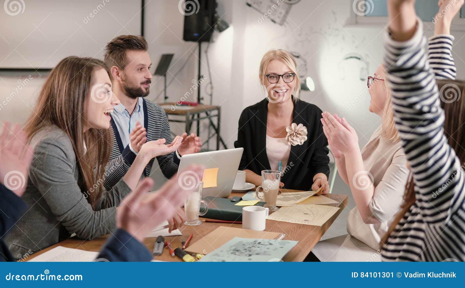 Il capo femminile ha riferito le buone notizie, ognuna è felice, alto--fiving gruppo di affari in un ufficio startup moderno
