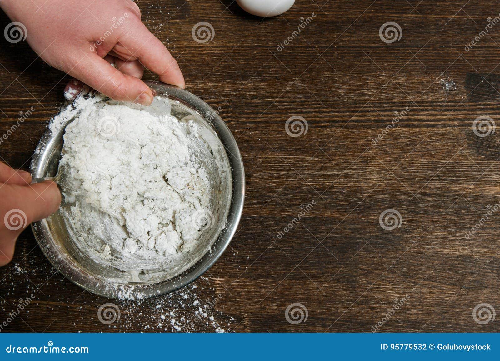 Il capo mescola la pasta in ciotola sulla tavola