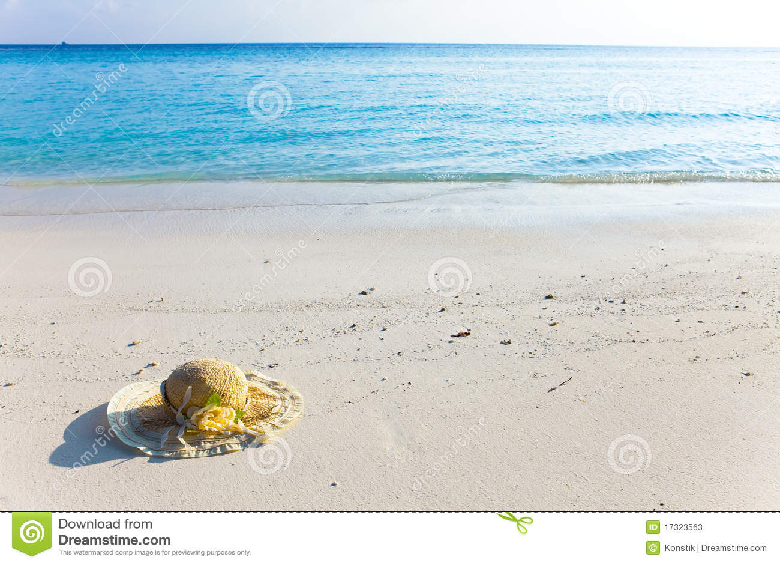 Il cappello di paglia pone sulla sabbia al bordo del mare