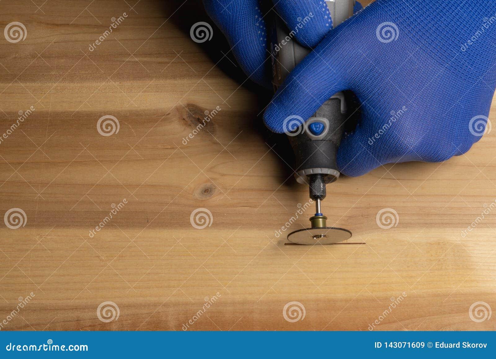 Il carpentiere in guanti protettivi blu tratta il dremel di legno
