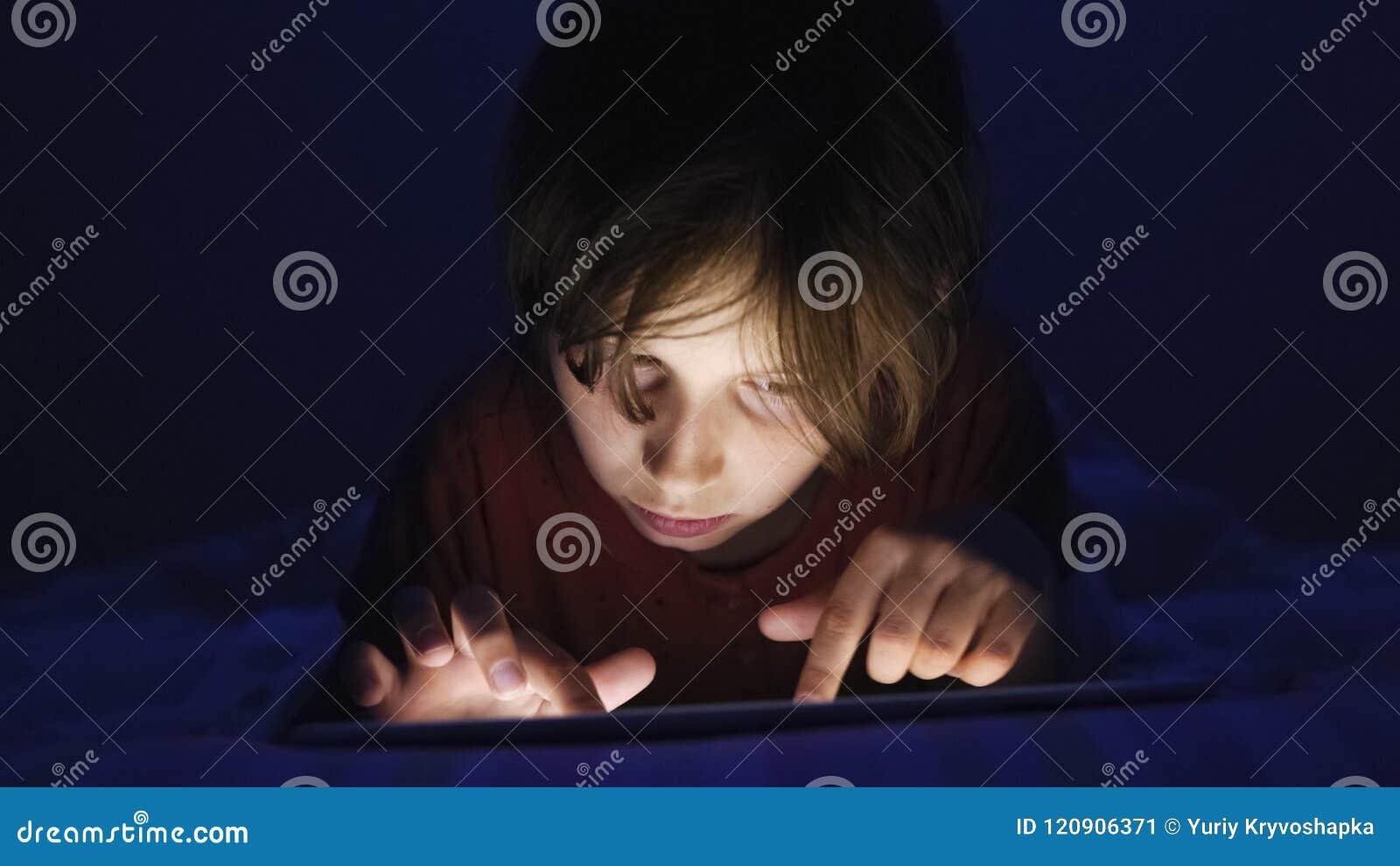 Il carrello ha sparato alla ragazza caucasica che si trova a letto giocando la compressa in Internet alla luce scura nell ambito
