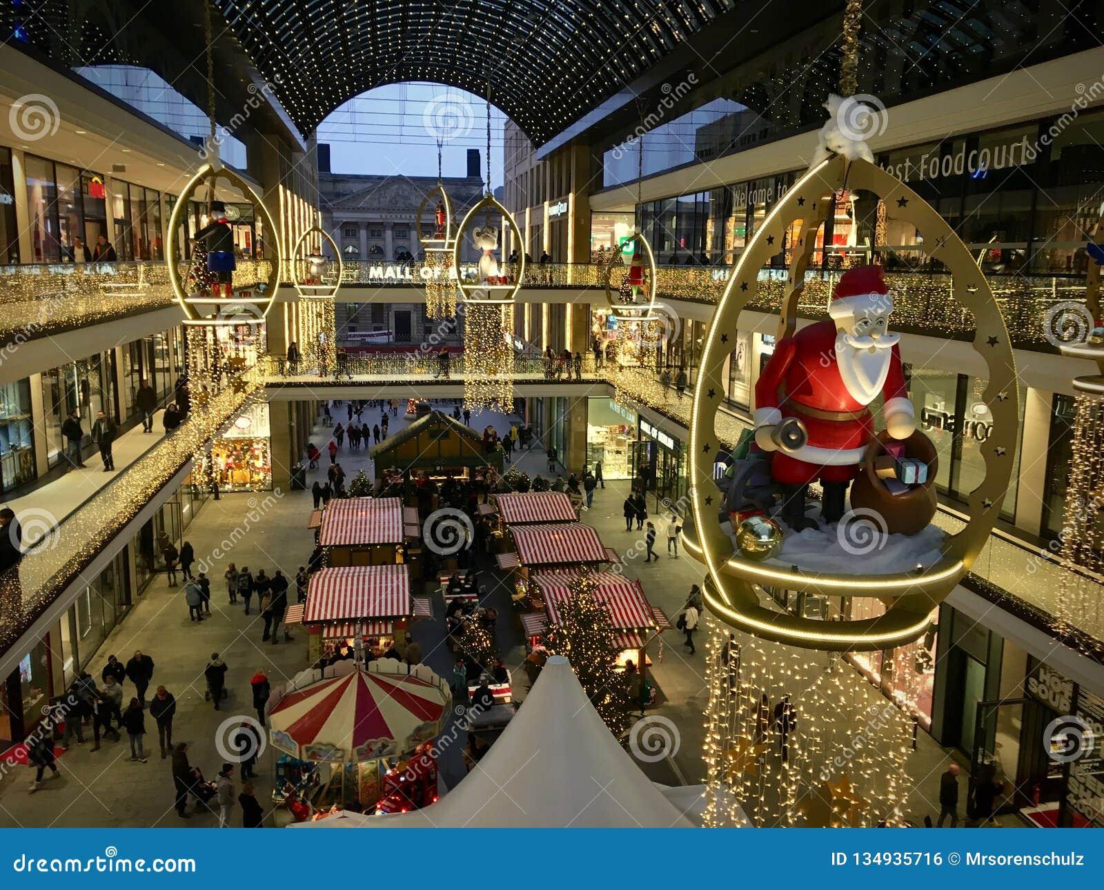 Il centro commerciale di Berlino ha decorato per il Natale con grande Santa Claus di legno, occupato con molti clienti