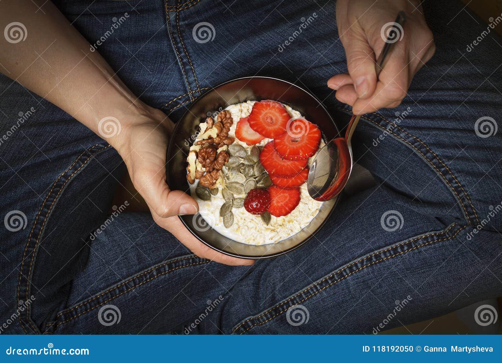 Il cibo sano, ciotola della prima colazione, yogurt, granola, semi, frutta fresca, ciotola, mano del ` s della donna, pulisce il