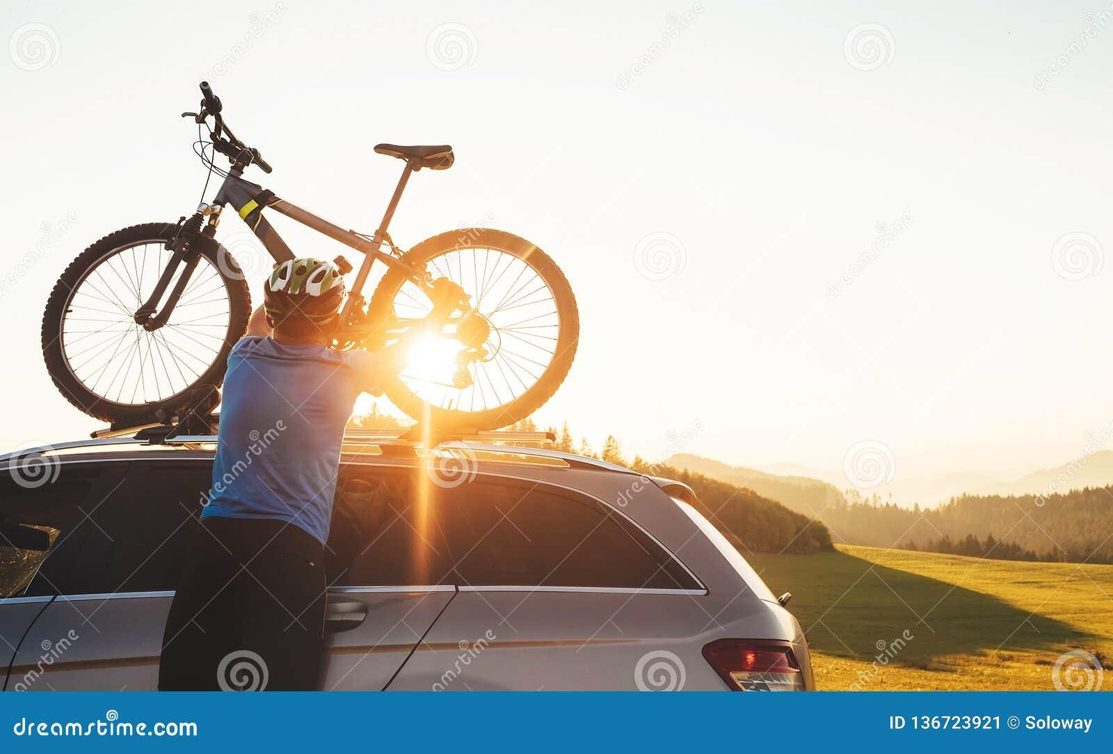 Il ciclista dell uomo veared in vestiti di riciclaggio ed in casco protettivo installa il suo mountain bike sul tetto dell automo