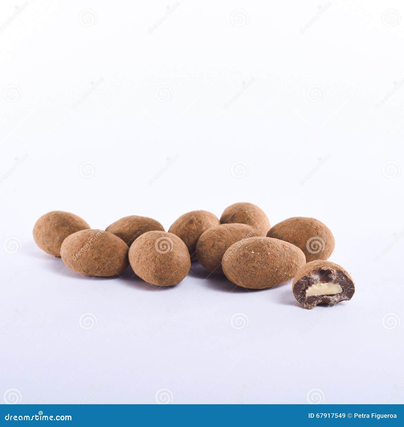 Il cioccolato e la cannella hanno coperto le mandorle sistemate su un fondo bianco