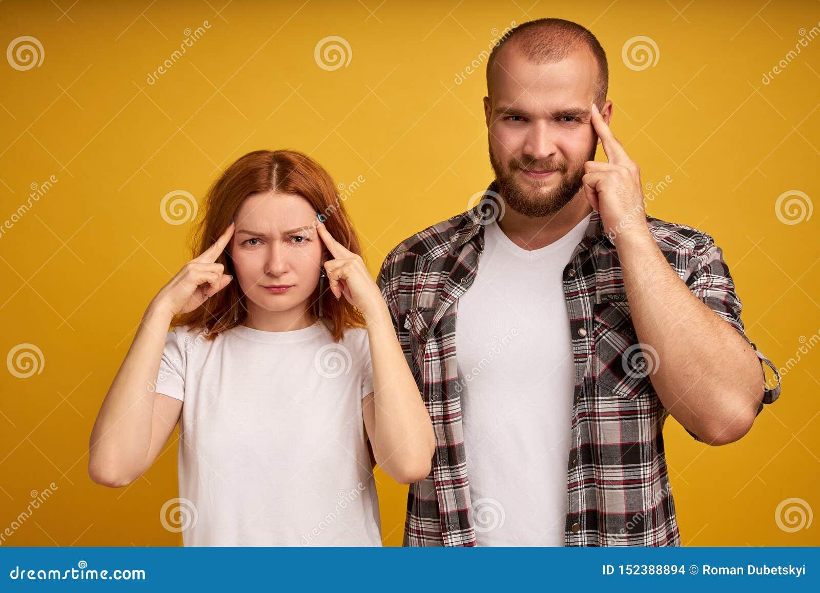 Il colpo dell interno della donna adulta premurosa frustrata e l uomo tengono le dita sulle tempie, provano a concentrarsi sulla