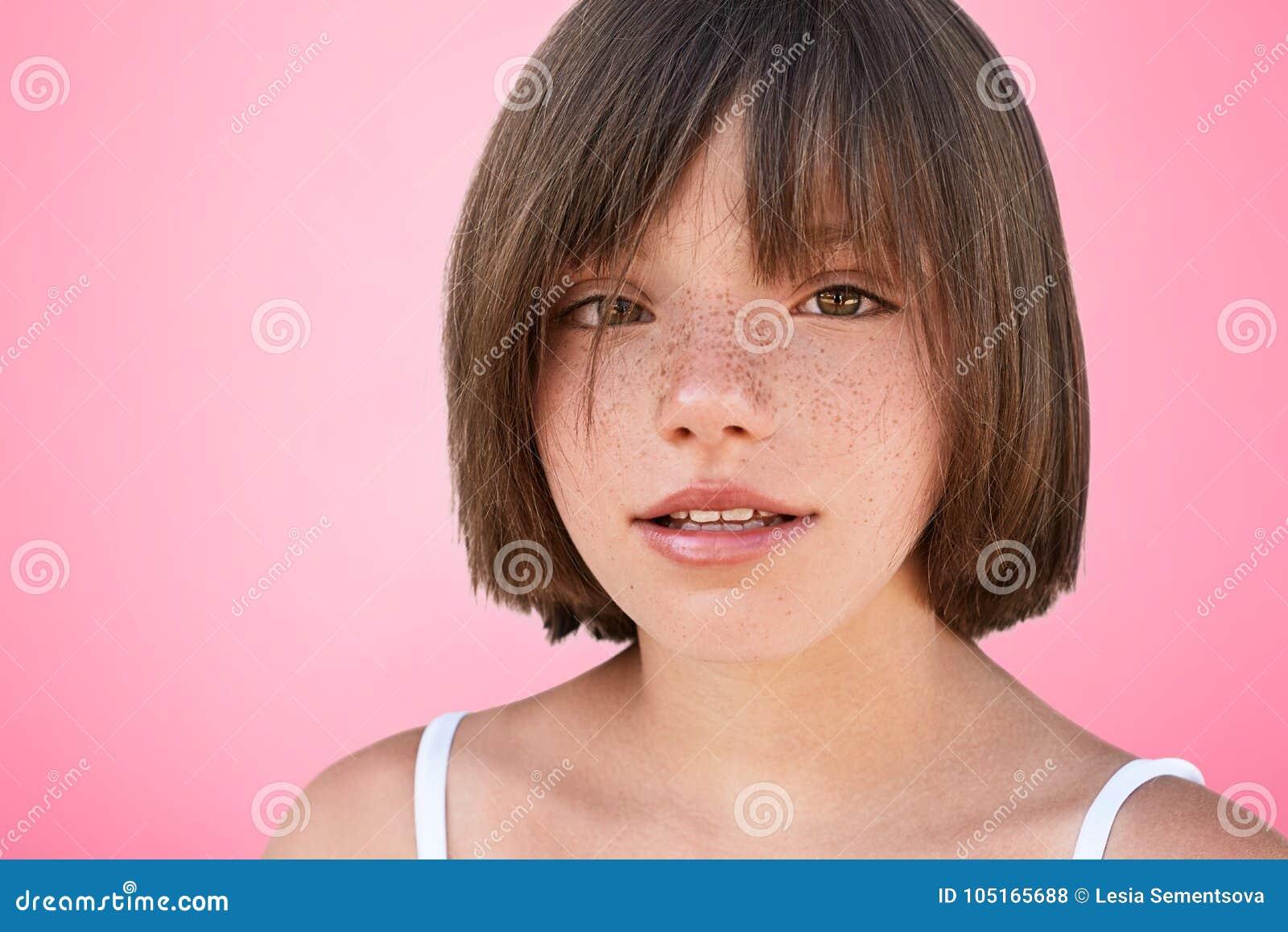Il colpo dell interno di bello piccolo bambino femminile freckled sicuro con l acconciatura ballonzolata esamina la macchina foto