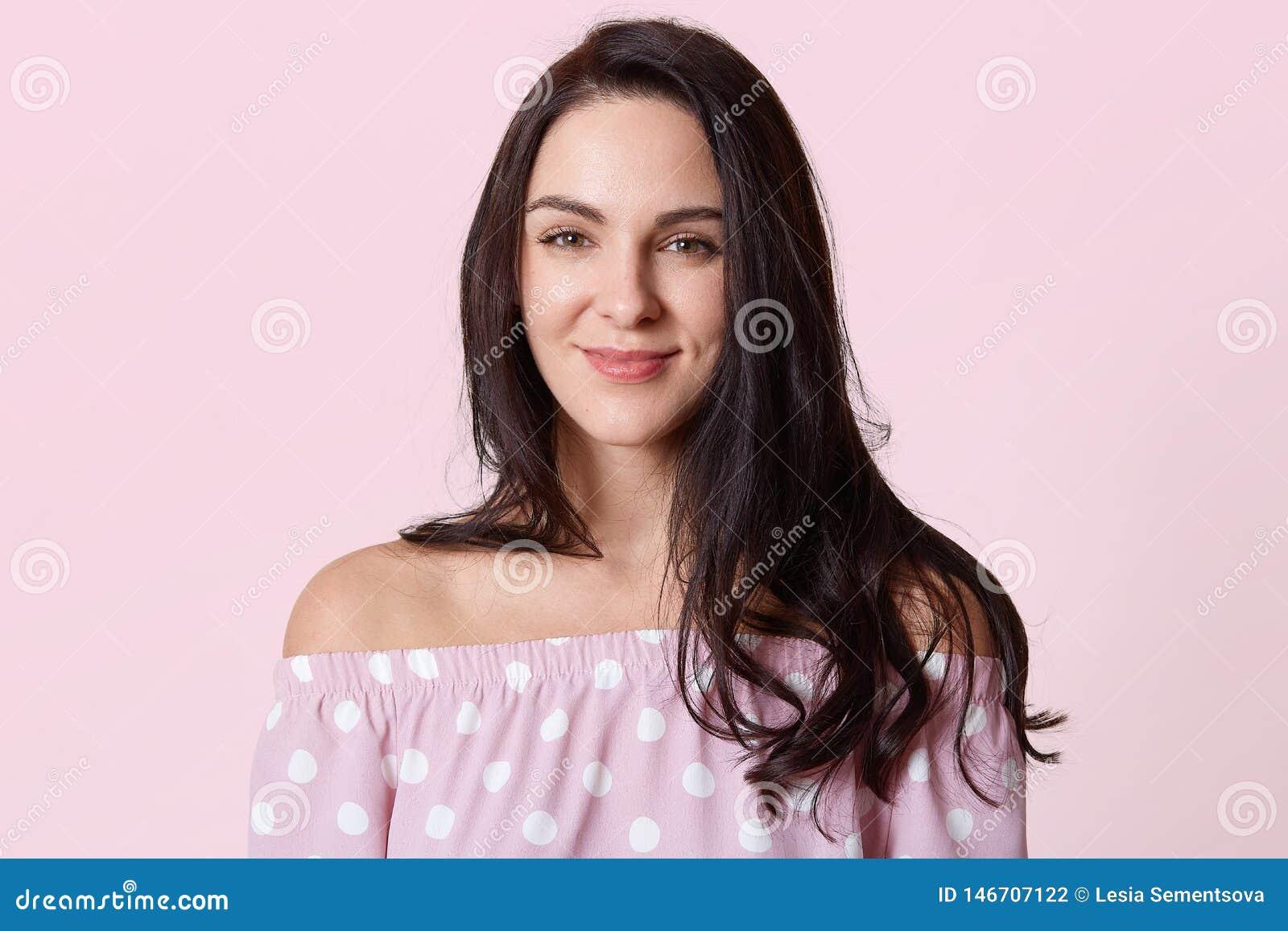 Il colpo di bella donna sorridente con pelle pulita, naturale compone, capelli castana lunghi che posano con le spalle nude, indo
