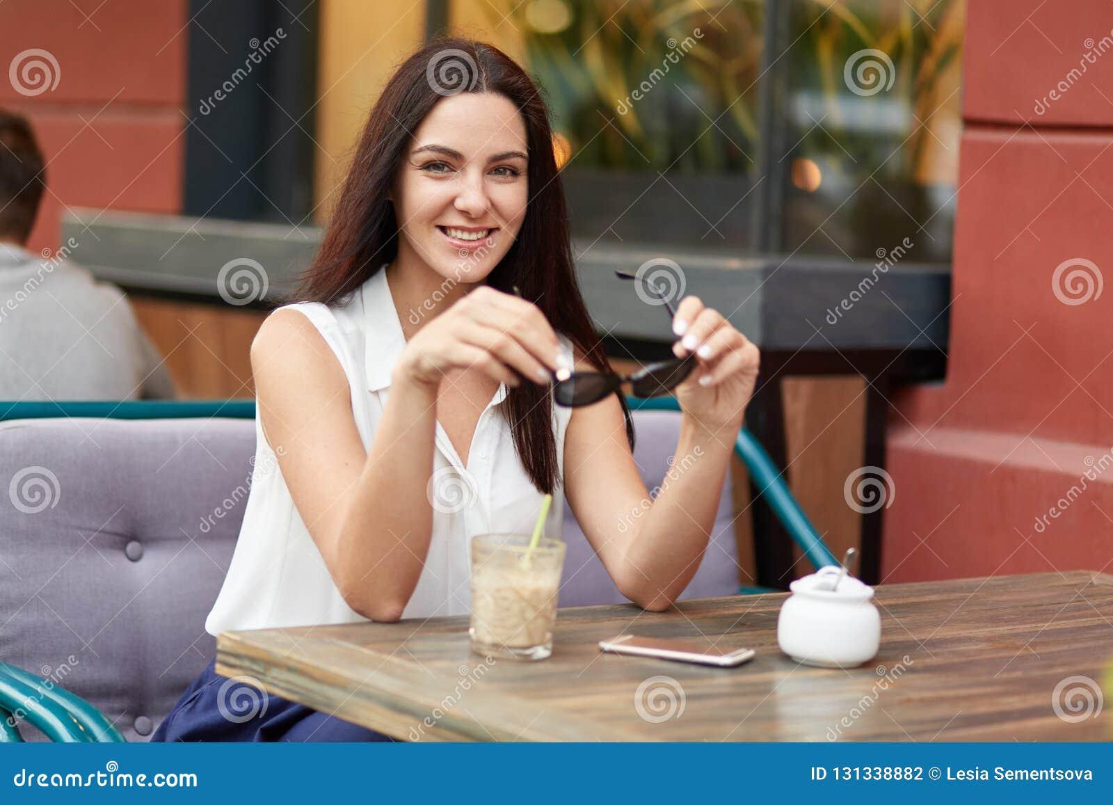 Il colpo orizzontale di bella donna europea rilassata tiene le tonalità, porta la blusa bianca, ha capelli lunghi, beve il cockta