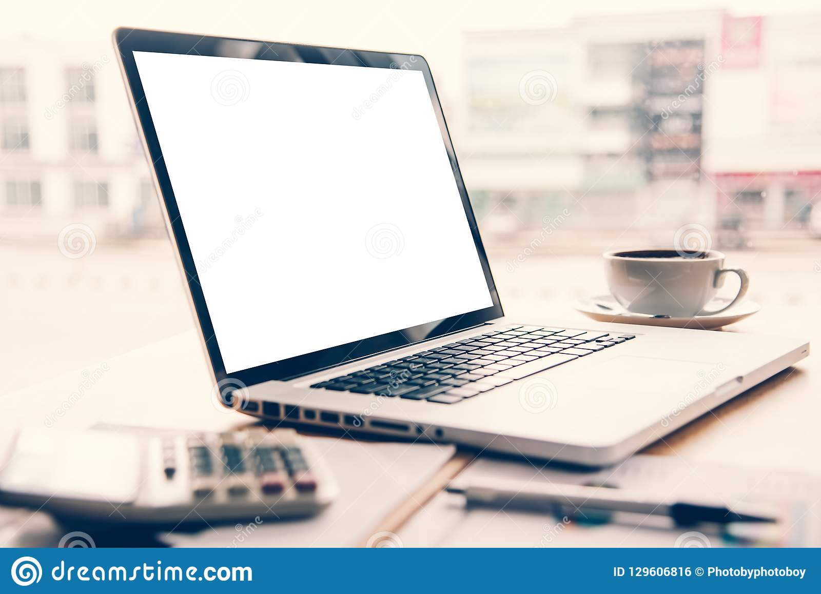 Il computer portatile è disposto su uno scrittorio con un calcolatore del caffè e della penna