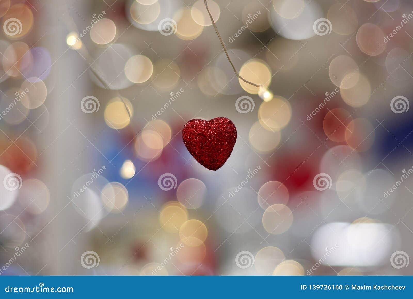 Il concetto di amore, cuore ha modellato il simbolo di amore che appende nell aria sul fondo del bokeh dalla ghirlanda