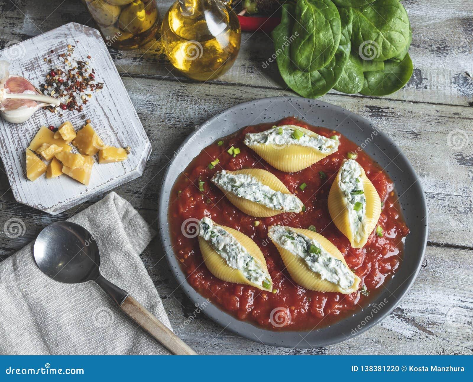 Il conchiglioni cucinato della pasta ha farcito gli spinaci ed il formaggio, salsa al pomodoro sul piatto