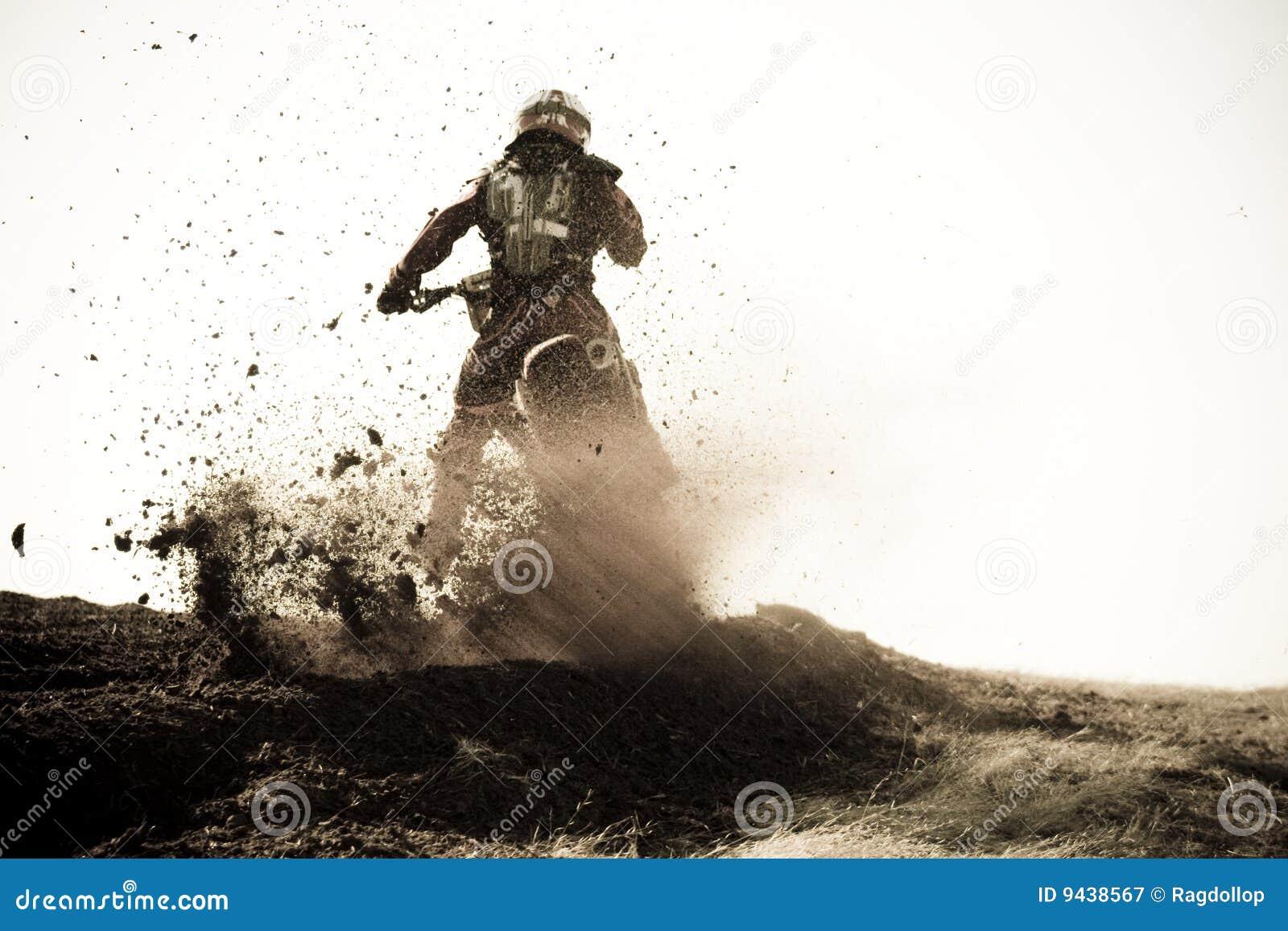 Il corridore di motocross roosts la banchina della sporcizia sulla pista.