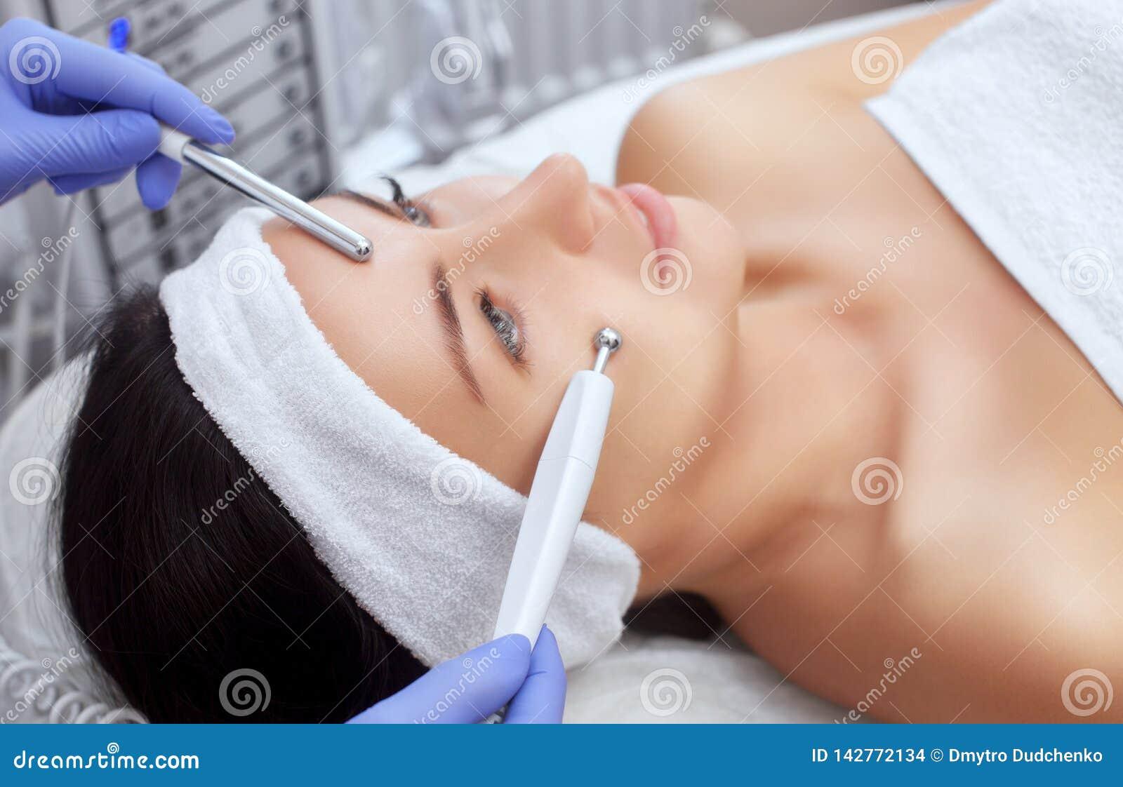 Il cosmetologo rende all apparato una procedura della terapia di un bello, giovane donna di Microcurrent in un salone di bellezza