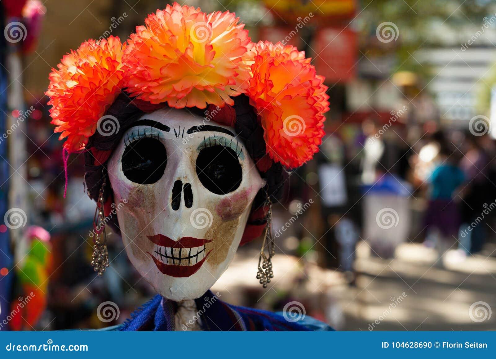 Il cranio dipinto e decorato con i fiori e gli orecchini di carta arancio del mache/ha decorato il cranio per Dia de los Muertos,