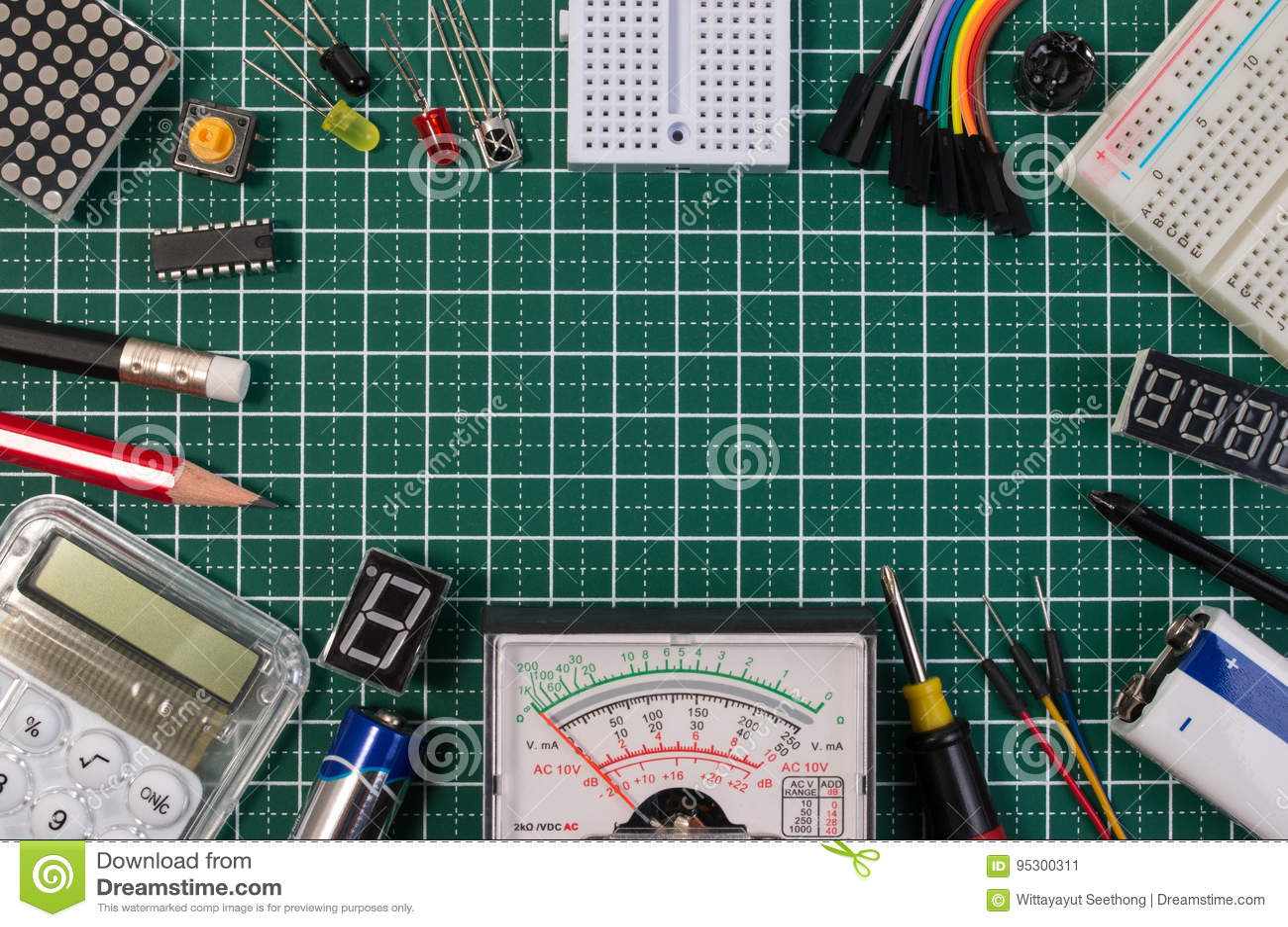 Il creatore elettrico di DIY foggia le componenti sul bordo di stuoia verde di taglio