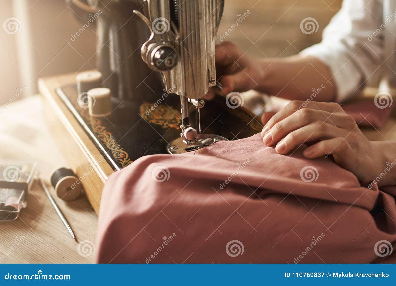 Il cucito tiene la mia mente rilassata Il colpo potato del sarto femminile che lavora al nuovo progetto, facente copre con la mac