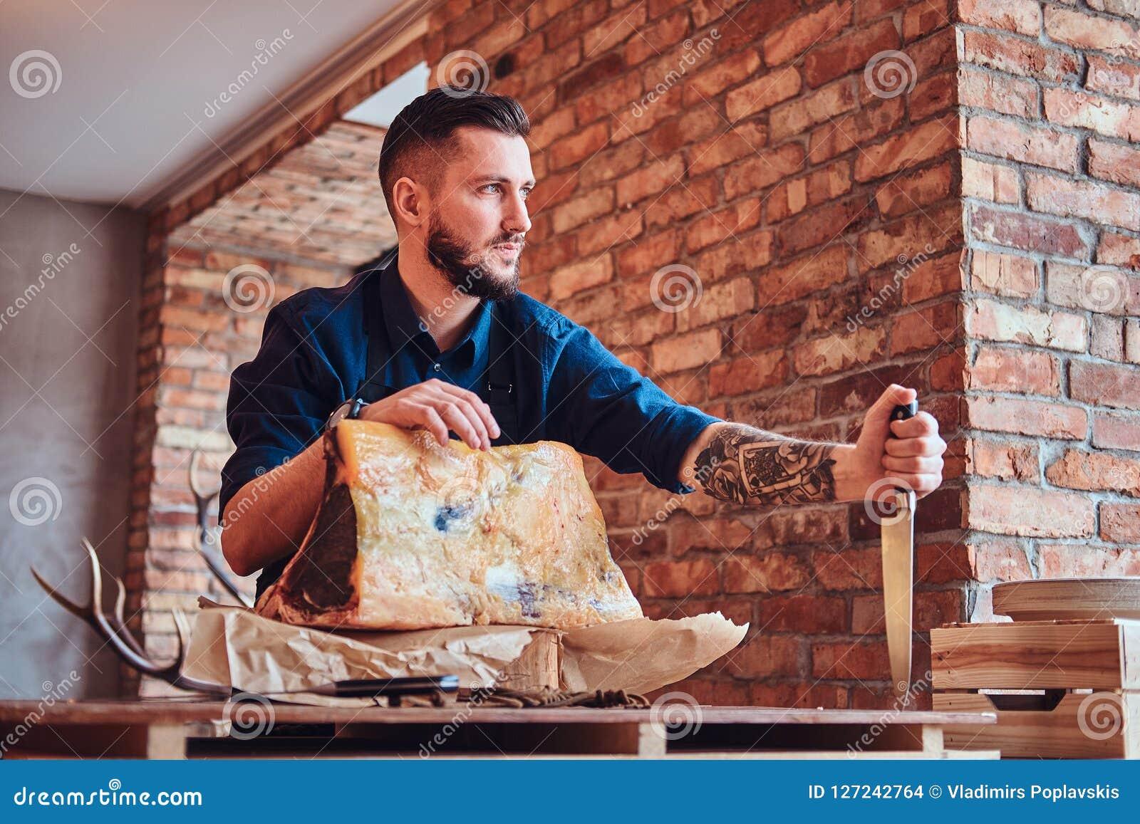 Il cuoco del cuoco unico tiene il coltello e la posa vicino ad una tavola con carne a scatti esclusiva in una cucina con l intern