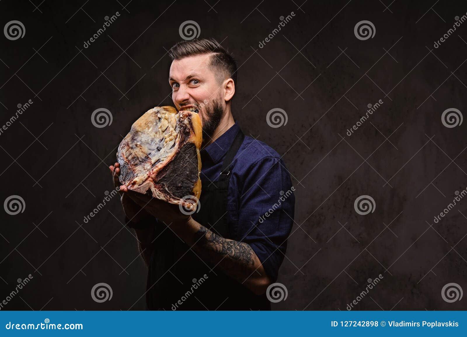 Il cuoco unico affamato morde il grande pezzo di carne curata esclusiva su fondo scuro