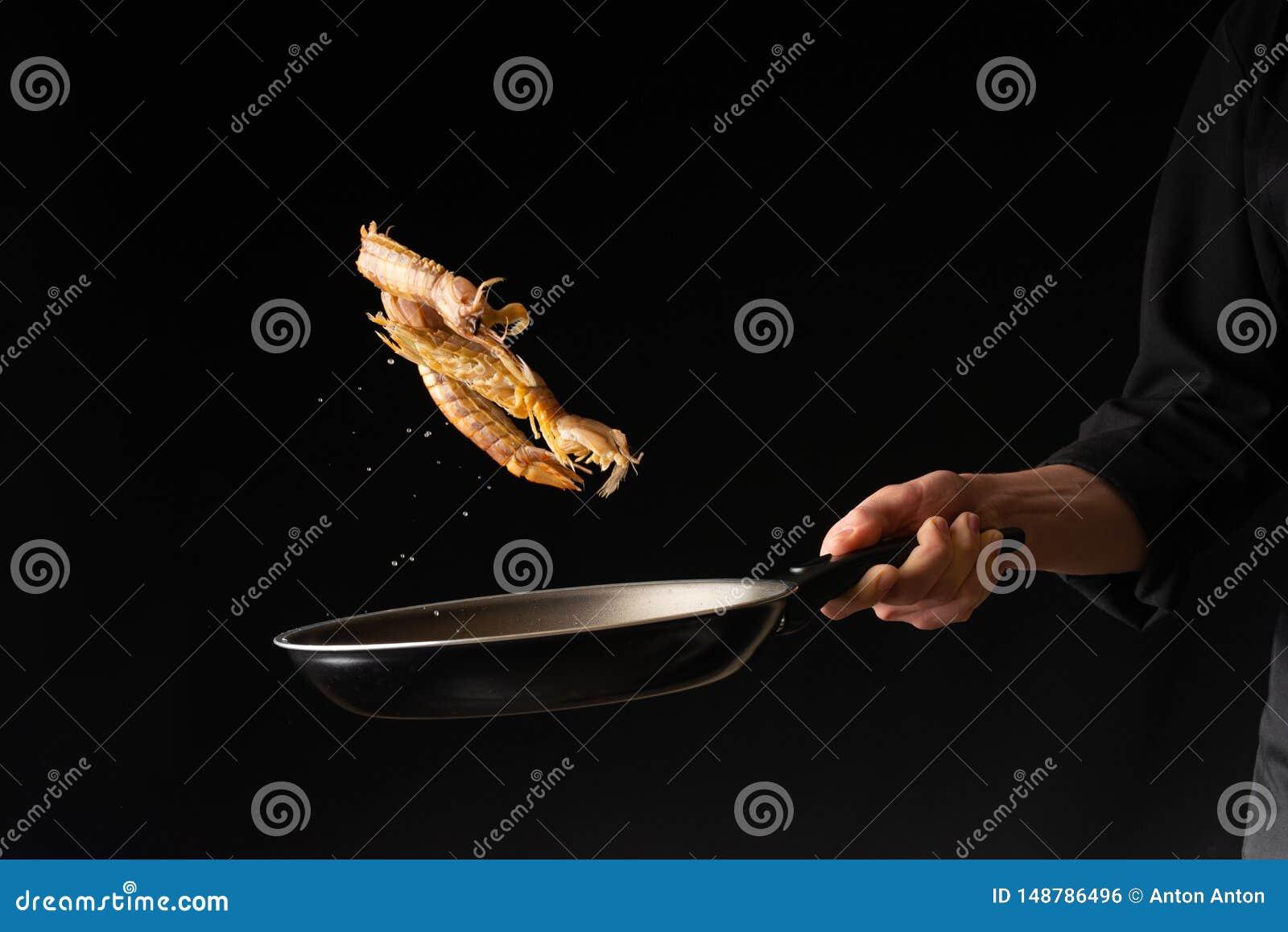 Il cuoco unico prepara i frutti di mare, gamberetto di mantide, cucina asiatica orientale, dilikates, su fondo nero, foto orizzon