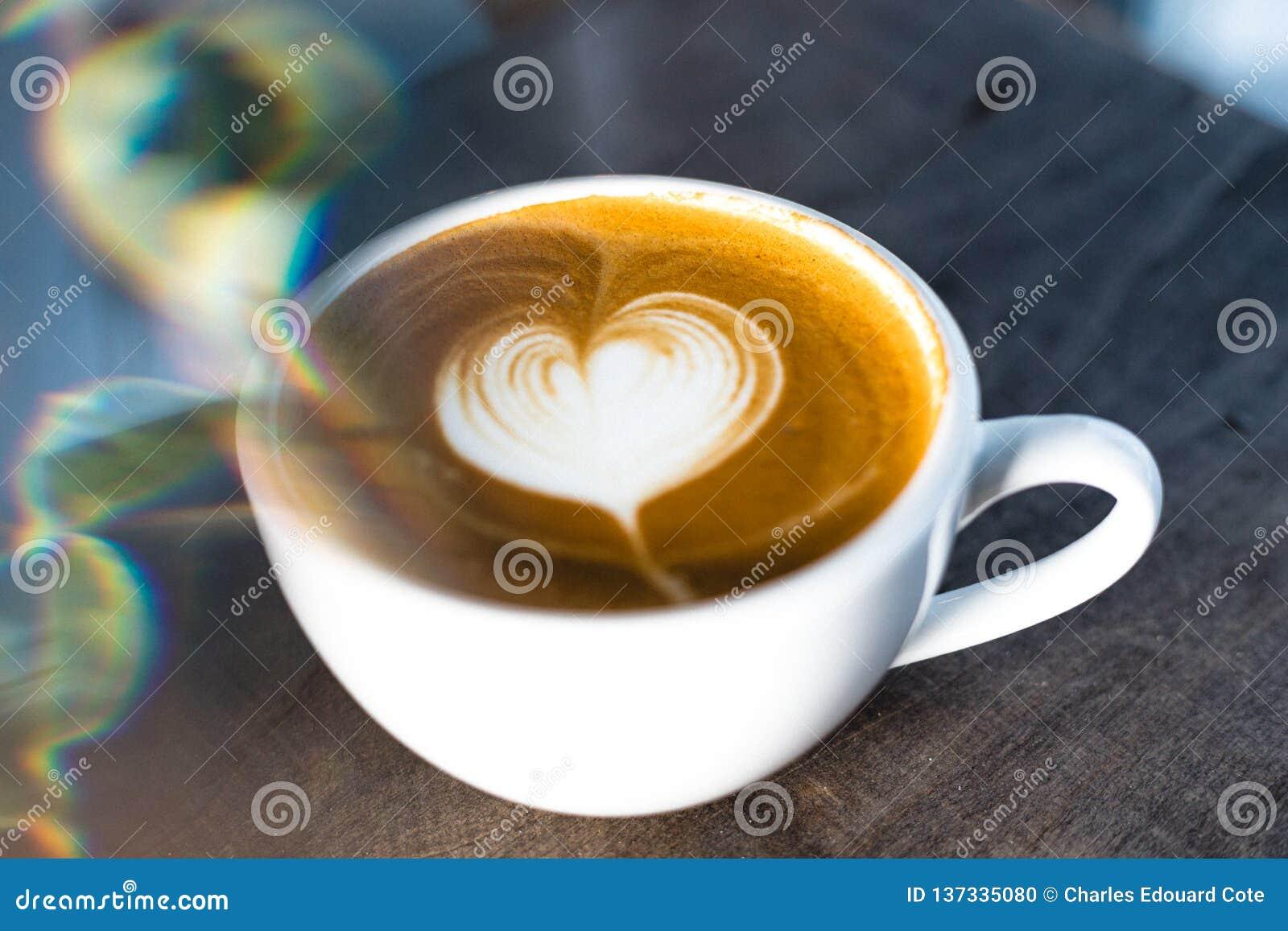 Il cuore ha modellato il latte del caffè sulla tavola di legno