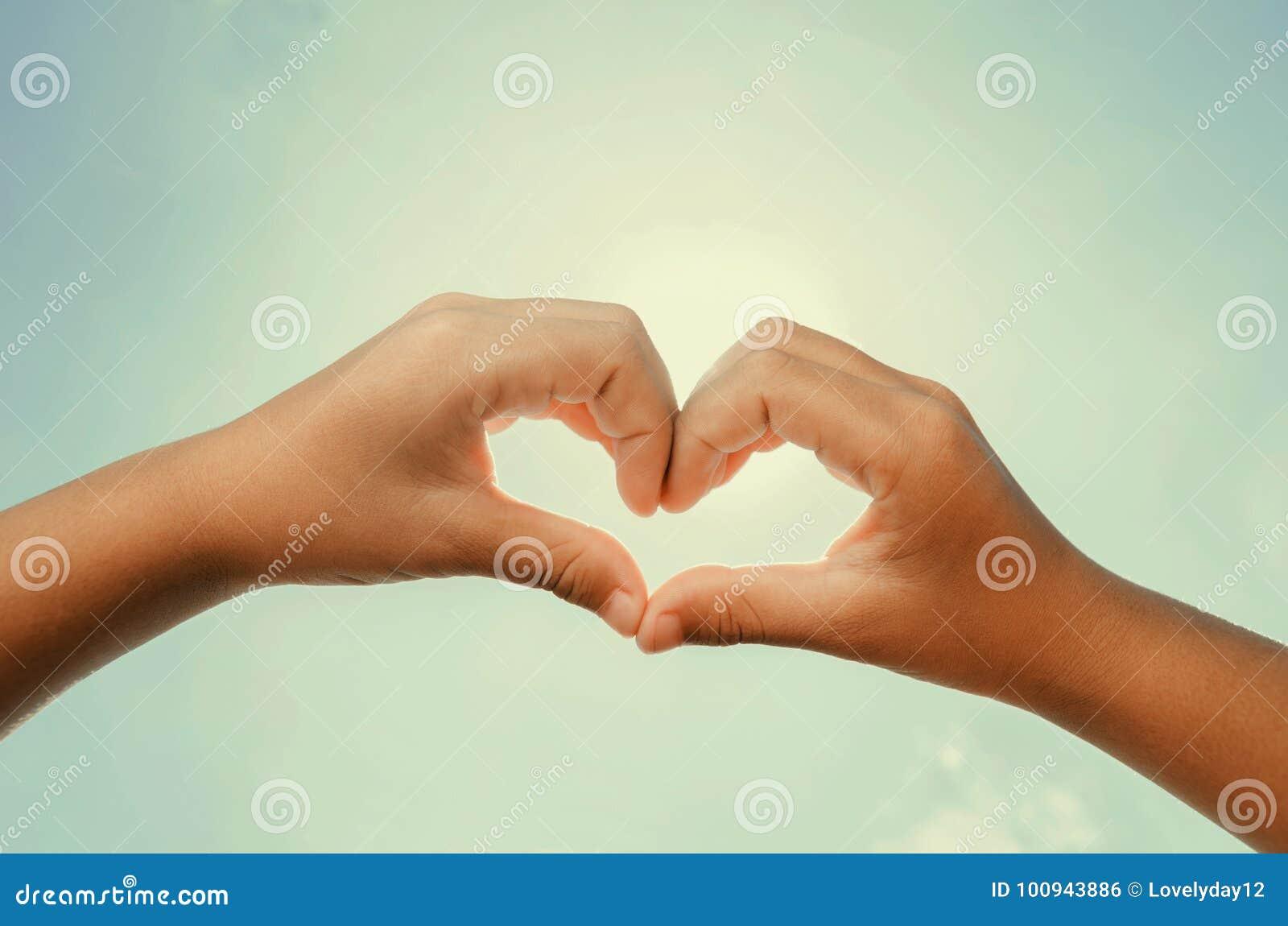 Il cuore ha modellato le mani con il instagram del sole e del cielo di mezzogiorno