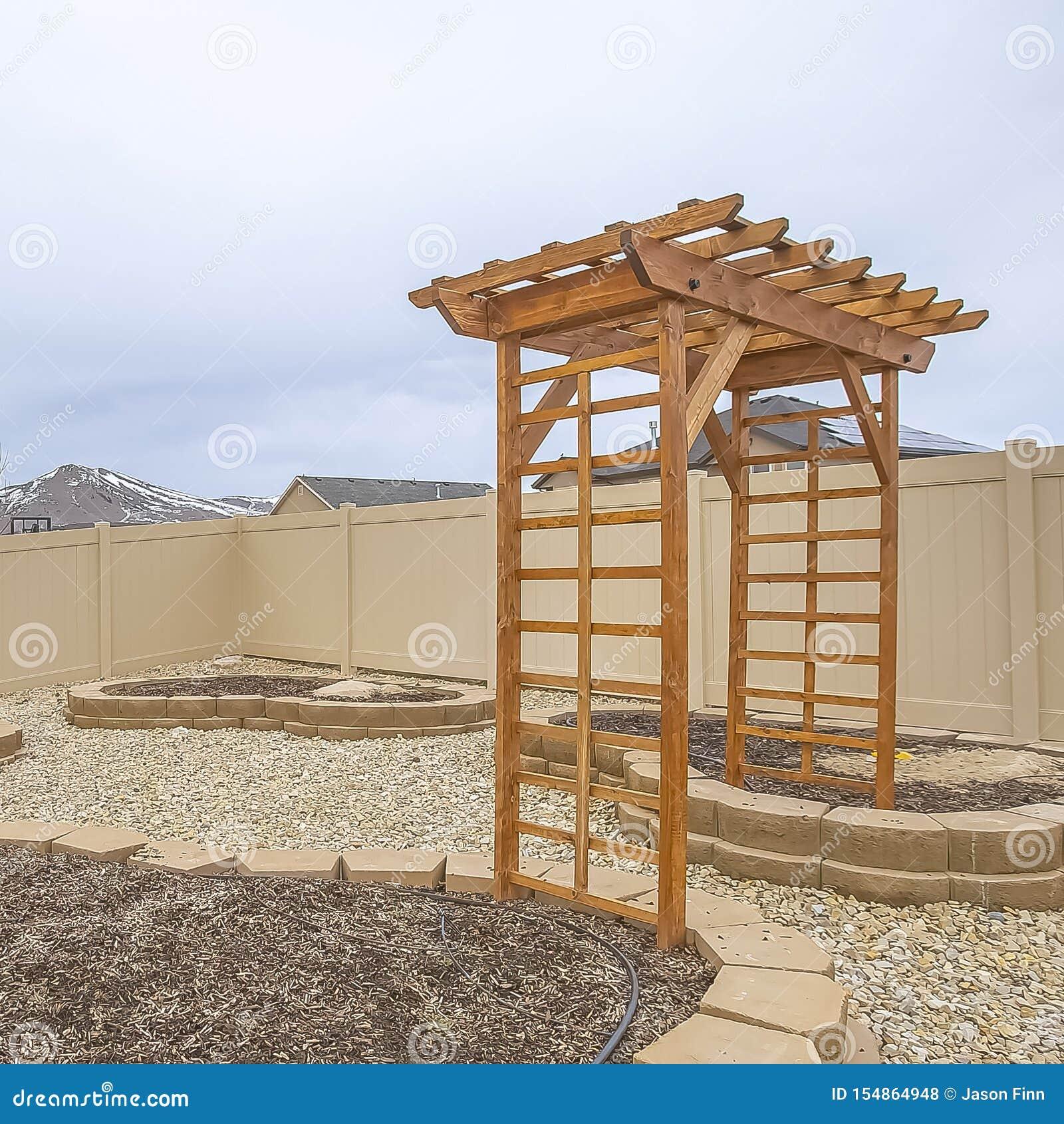 Il cuore quadrato ha modellato i letti di piantatura ed il supporto conico di legno all iarda di una casa
