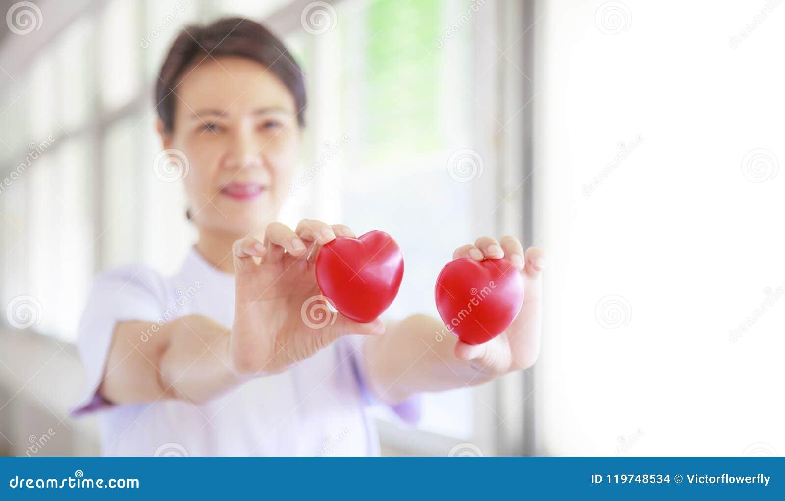 Il cuore rosso ha tenuto dalla mano femminile sorridente del ` s dell infermiere, rappresentante dando la mente di servizio di al