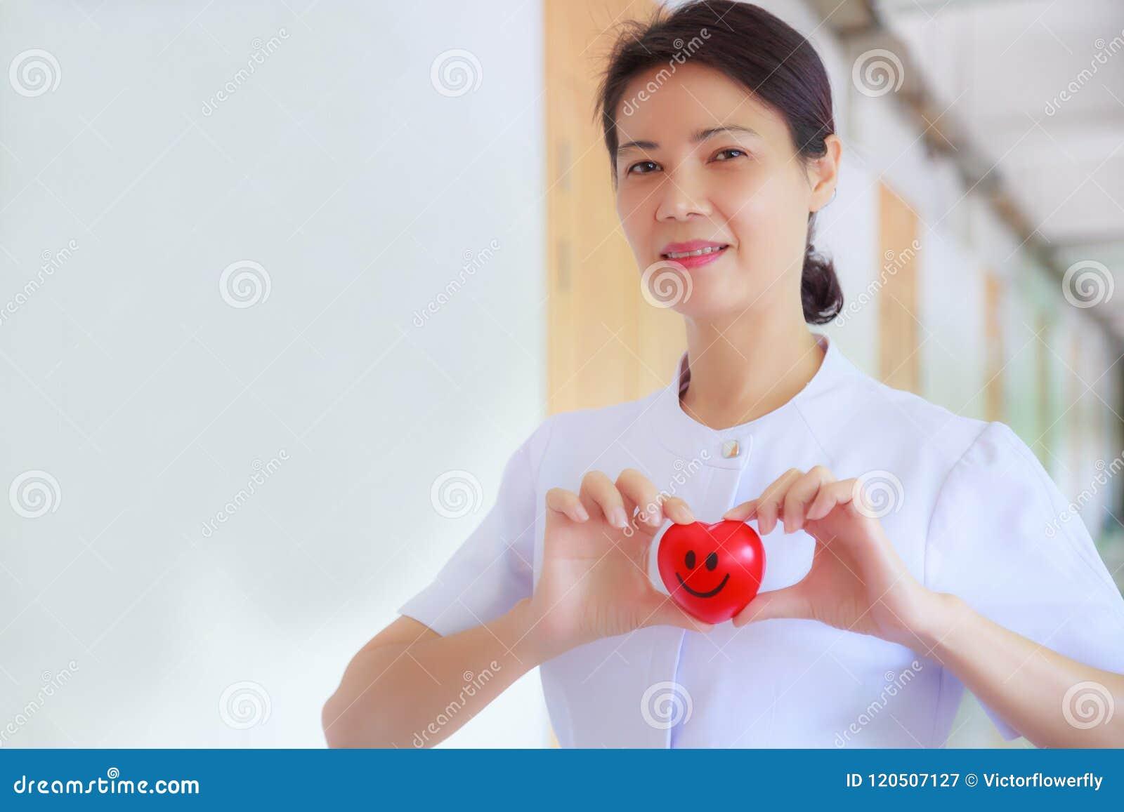 Il cuore rosso sorridente ha tenuto dalla mano femminile sorridente del ` s dell infermiere nell ospedale o nella clinica di sani