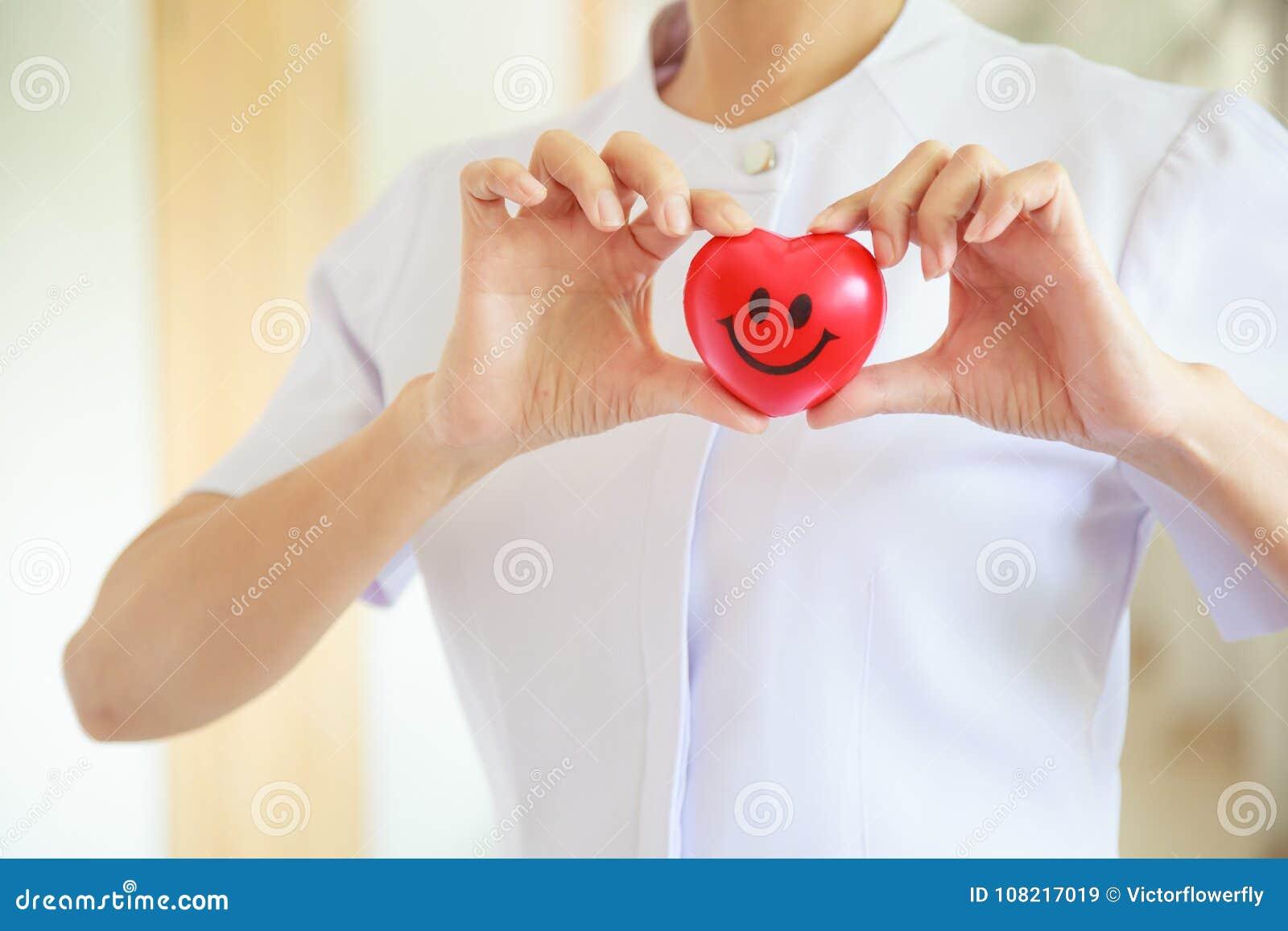Il cuore sorridente rosso ha tenuto dal ` femminile s dell infermiere entrambe le mani, rappresentanti dando la mente di servizio