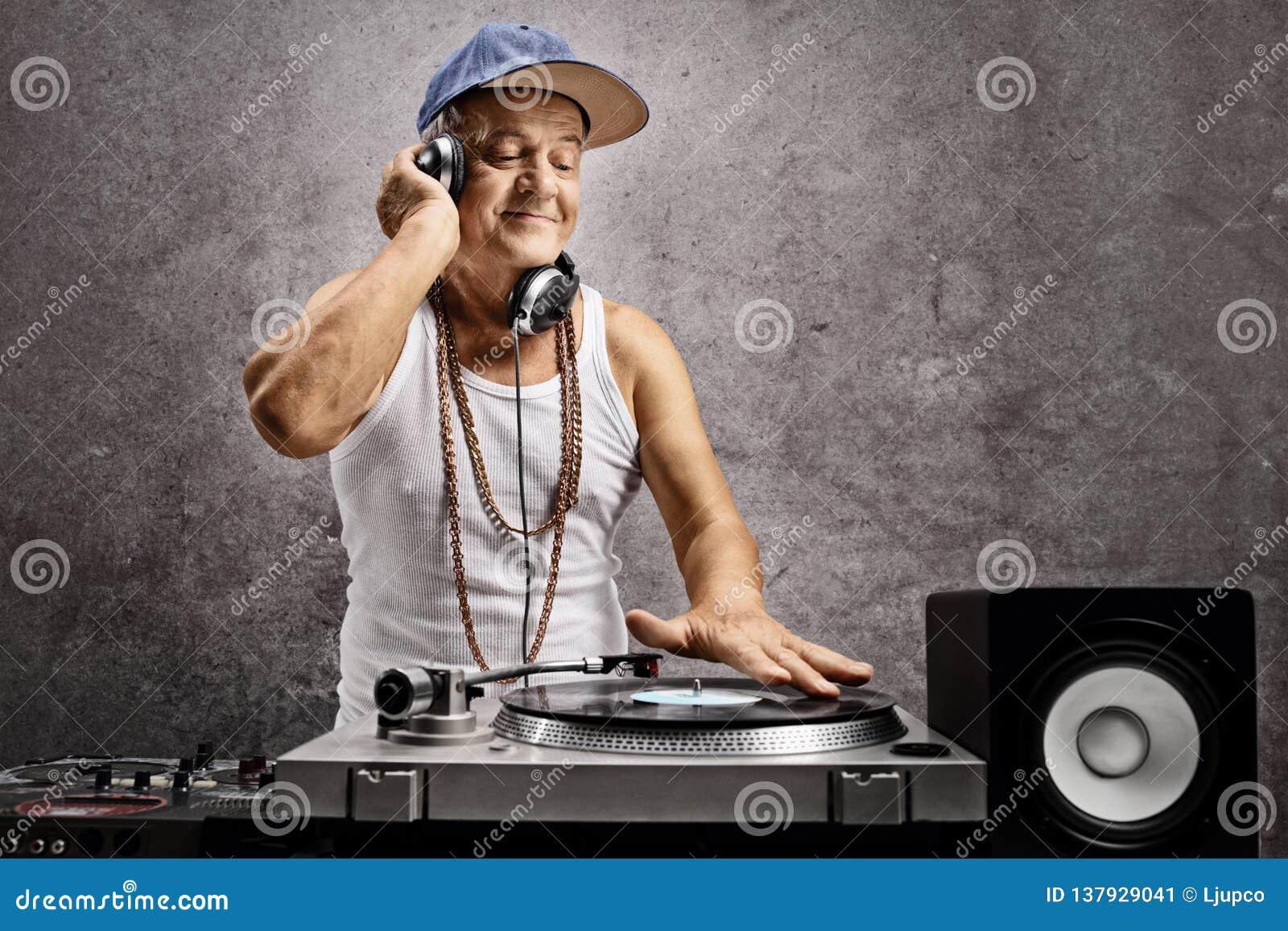 Il DJ maturo con le cuffie che giocano musica ad una piattaforma girevole