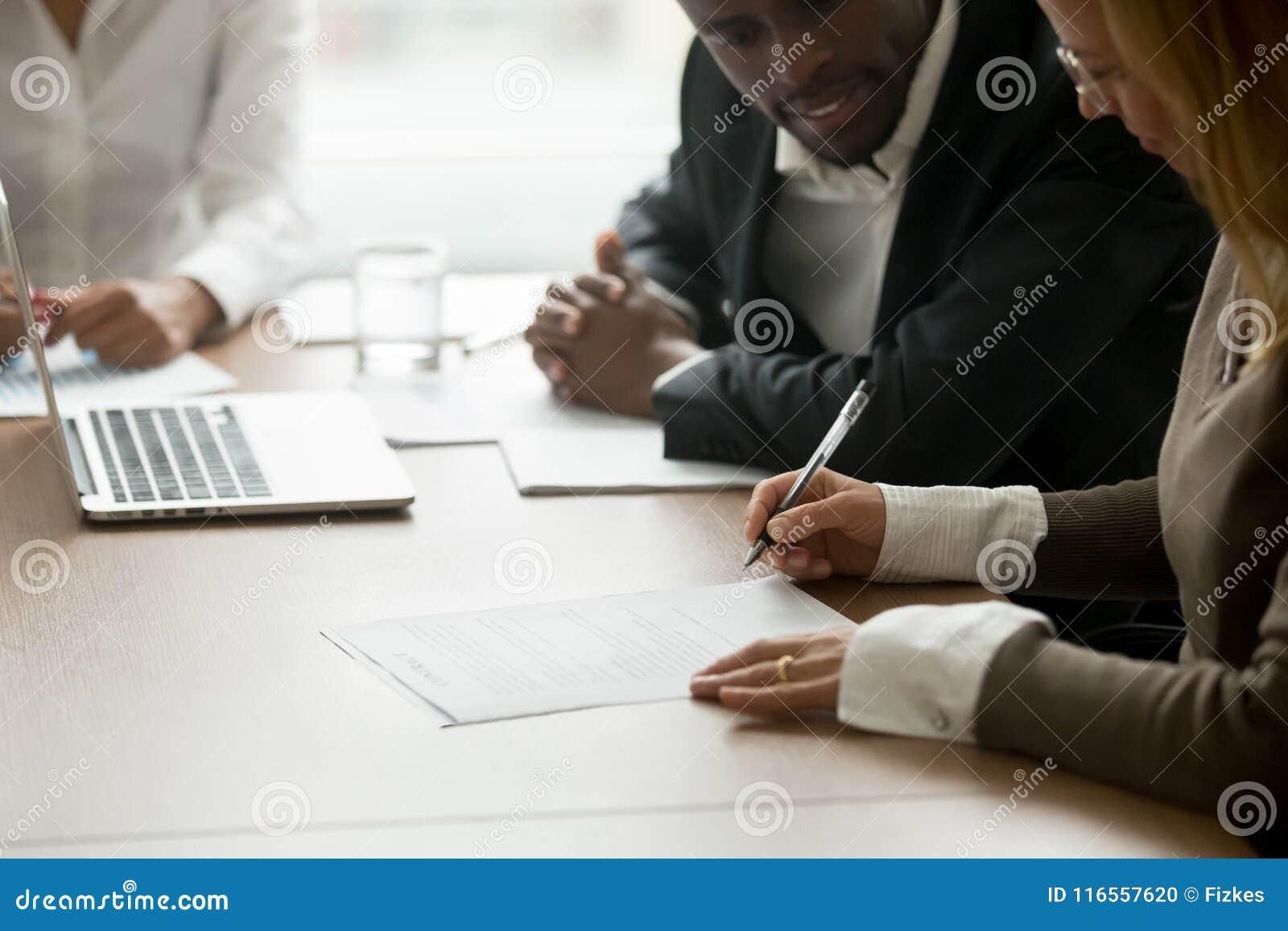Il documento di firma di affari della donna di affari ai diversi partner si incontra