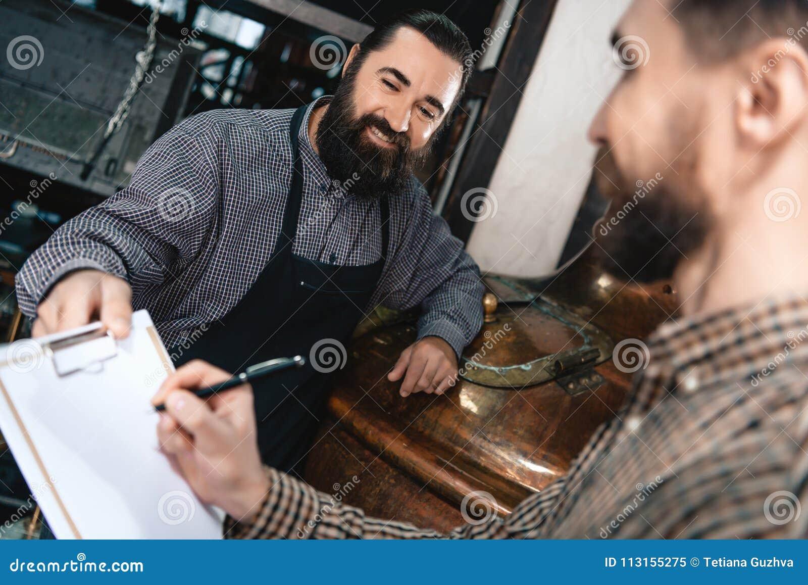 Il fabbricante di birra barbuto contento in grembiule dà i documenti per l uomo di firma in camicia in fabbrica di birra
