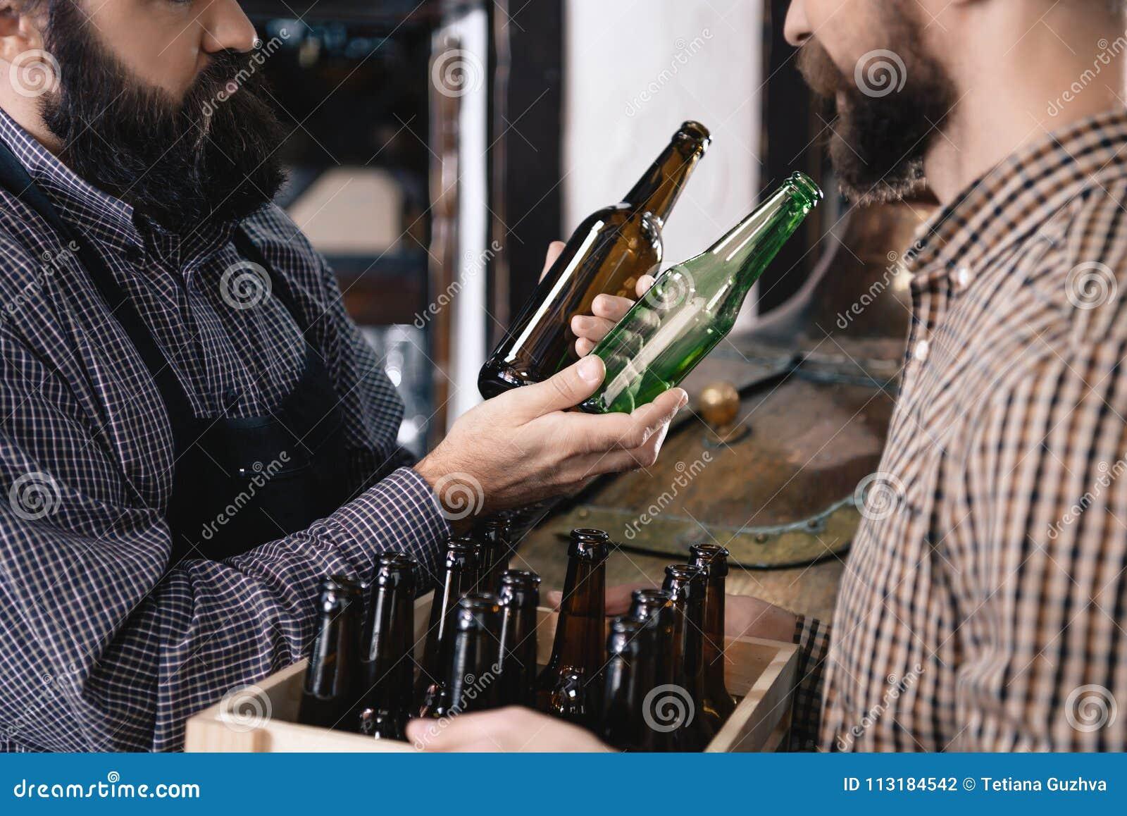 Il fabbricante di birra barbuto prende la bottiglia di birra di vetro di colore in fabbrica di birra Processo di fabbricazione de