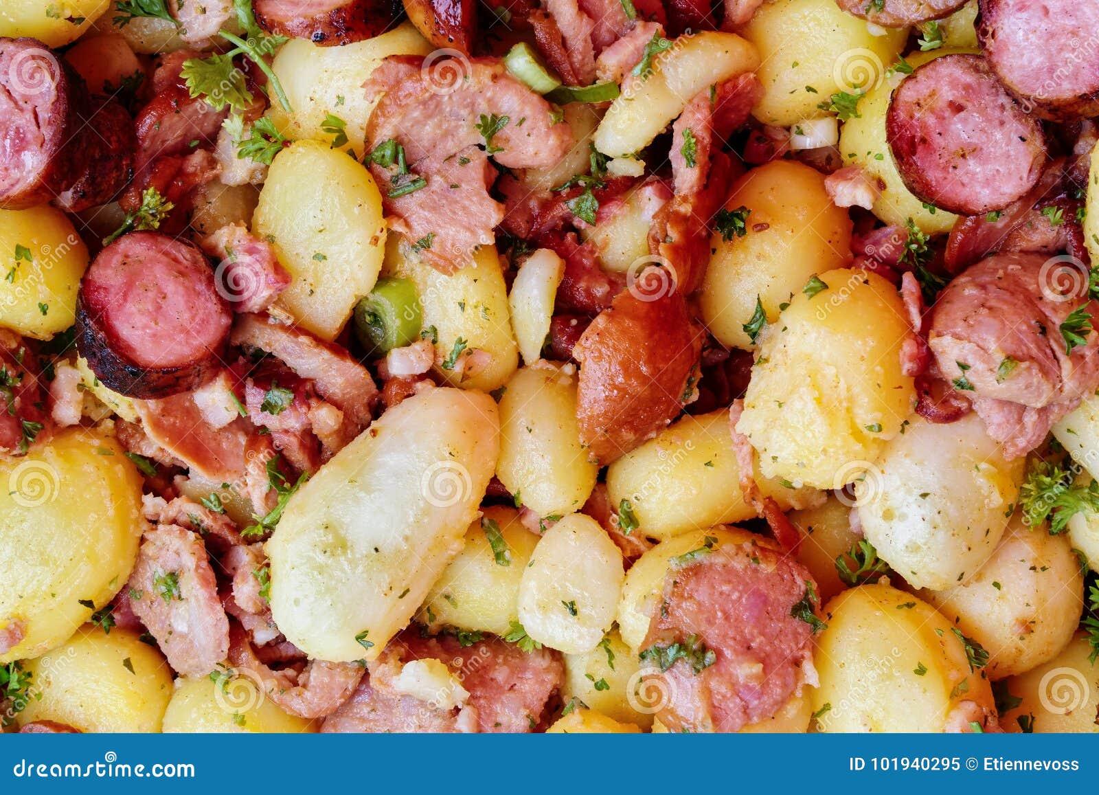 Il fondo della patata cucinata, la carne affumicata e la salsiccia si mescolano