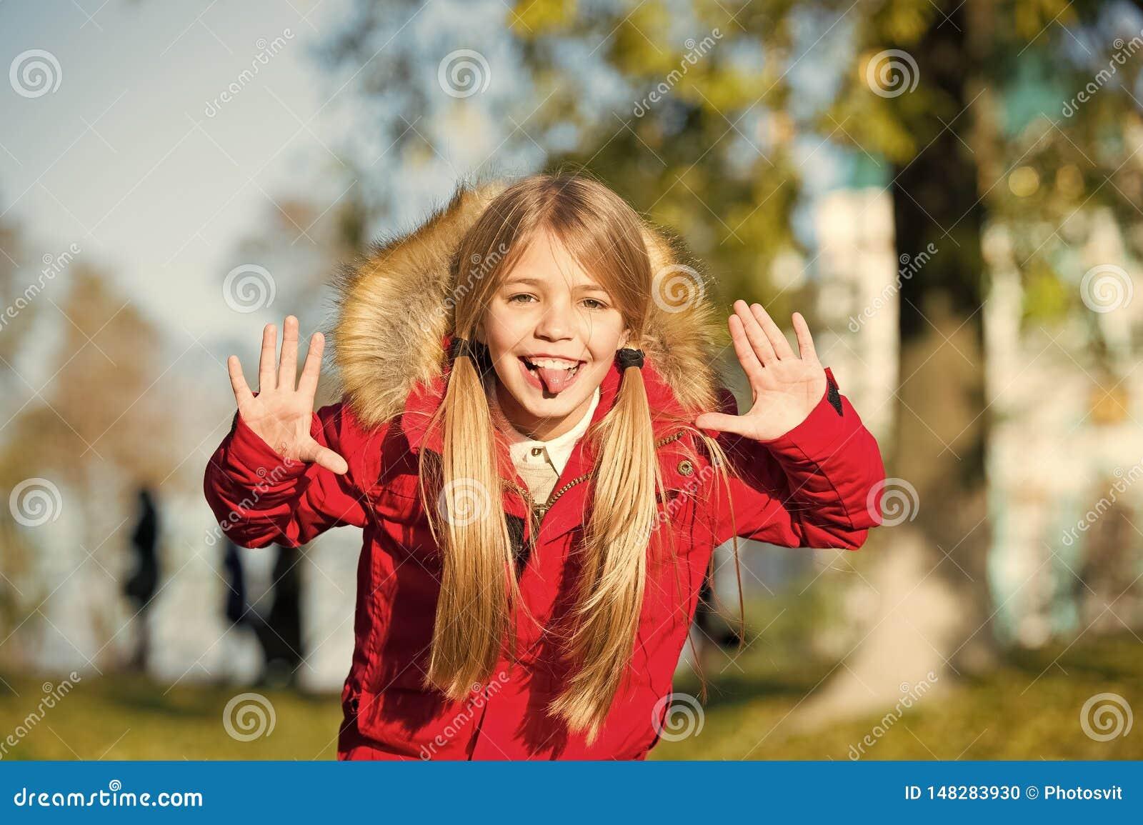 Il fronte allegro dello smorfia della ragazza in cappotto gode del parco di caduta Svago allegro del bambino Capelli lunghi biond