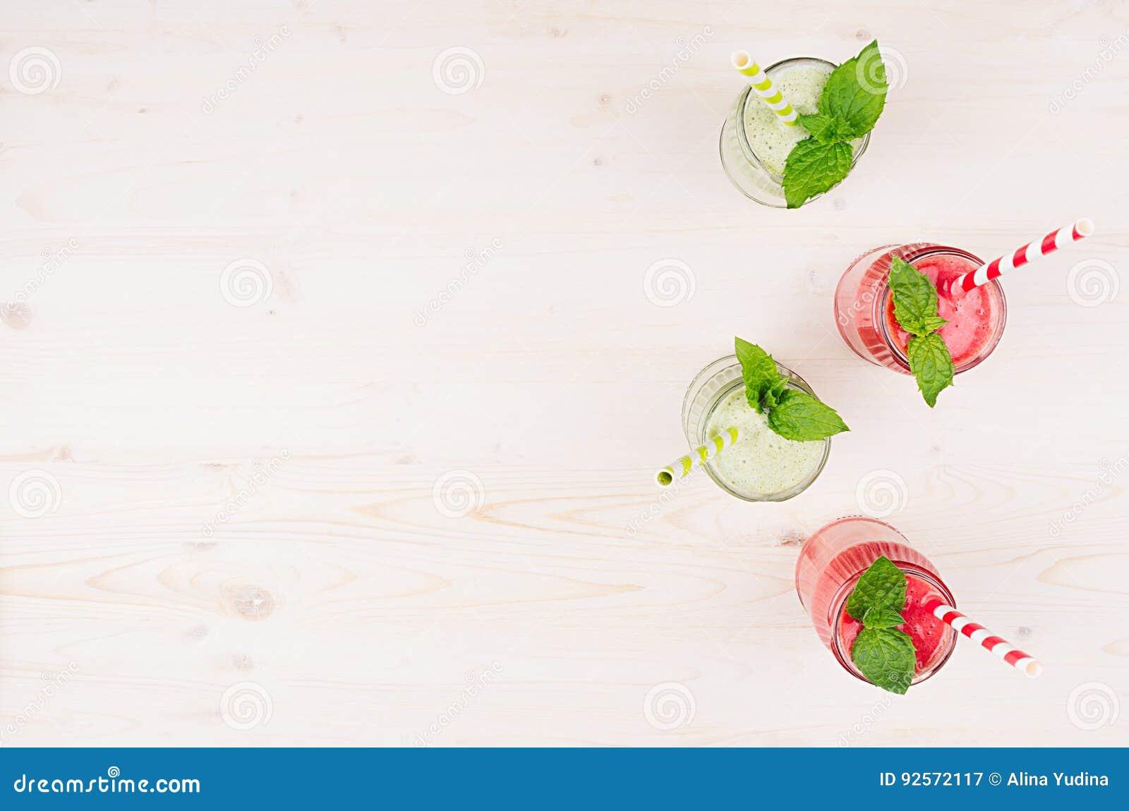 Il frullato verde e rosso di recente mescolato della frutta in barattoli di vetro con paglia, menta copre di foglie, vista superi