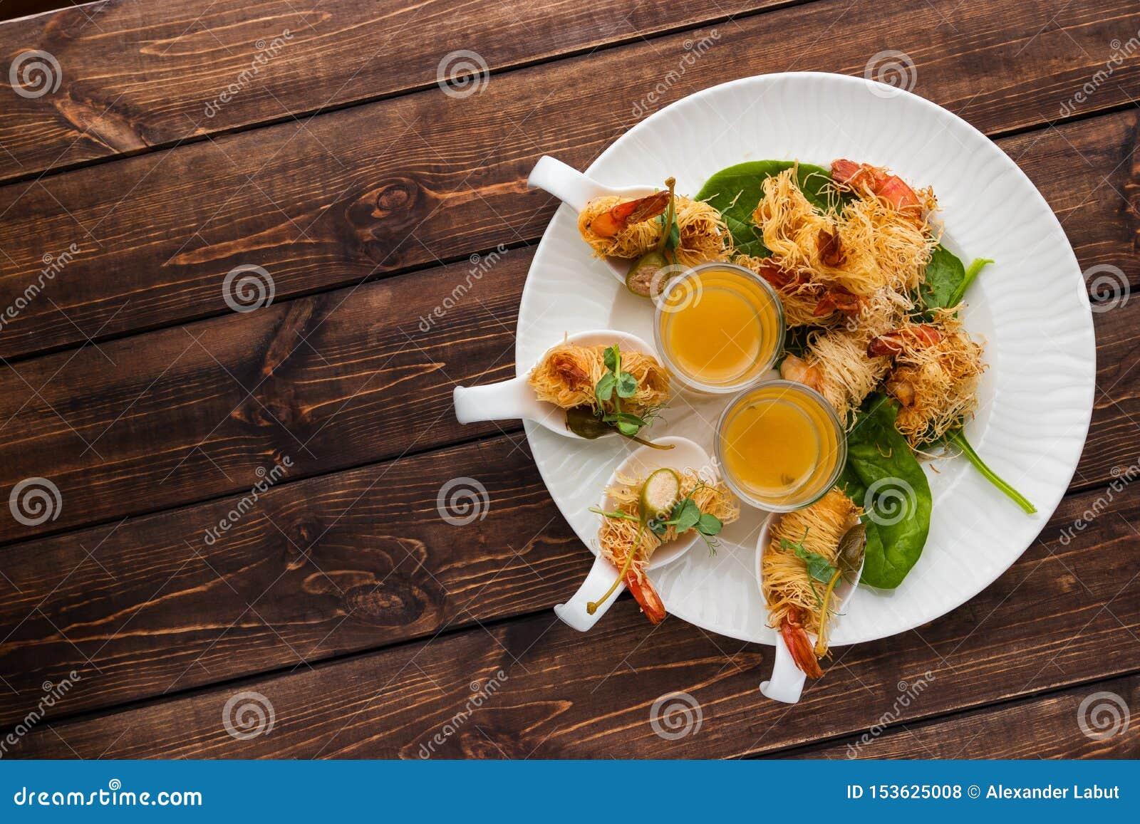 Il gamberetto croccante in crosta di Kataifi ed il timo con Champagne Sauce in vetri si trovano su un piatto bianco su un fondo l