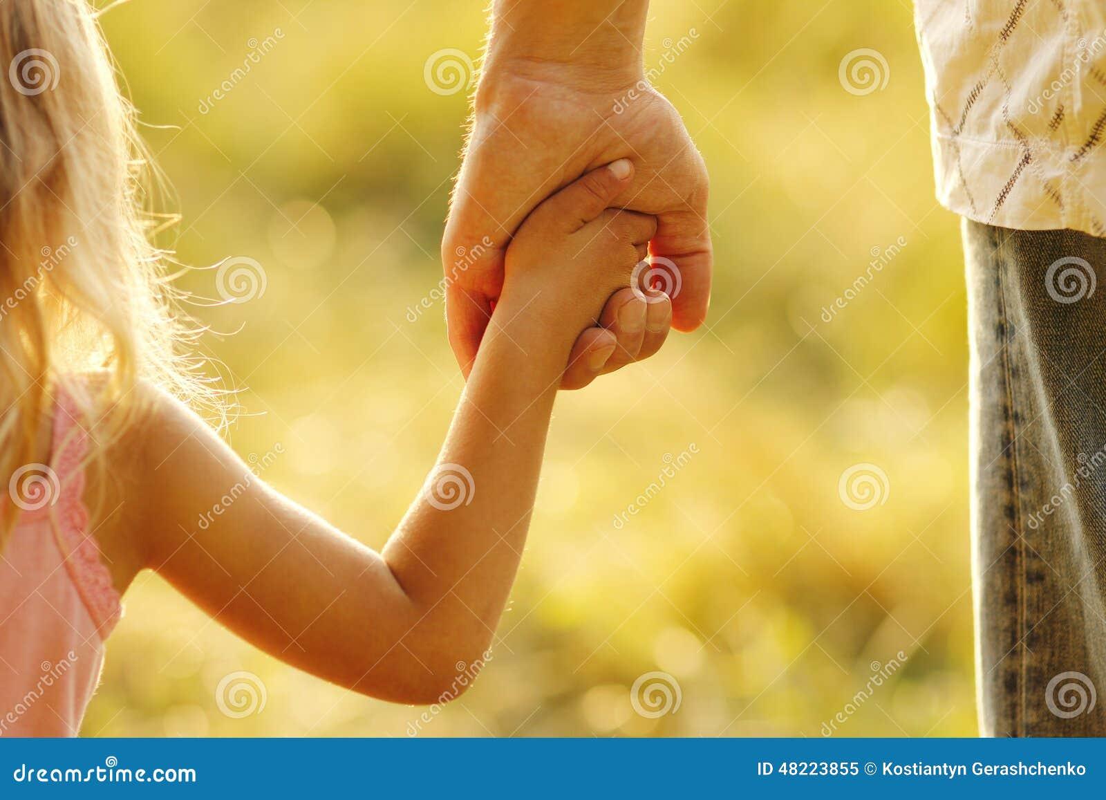 Il genitore tiene la mano di piccolo bambino