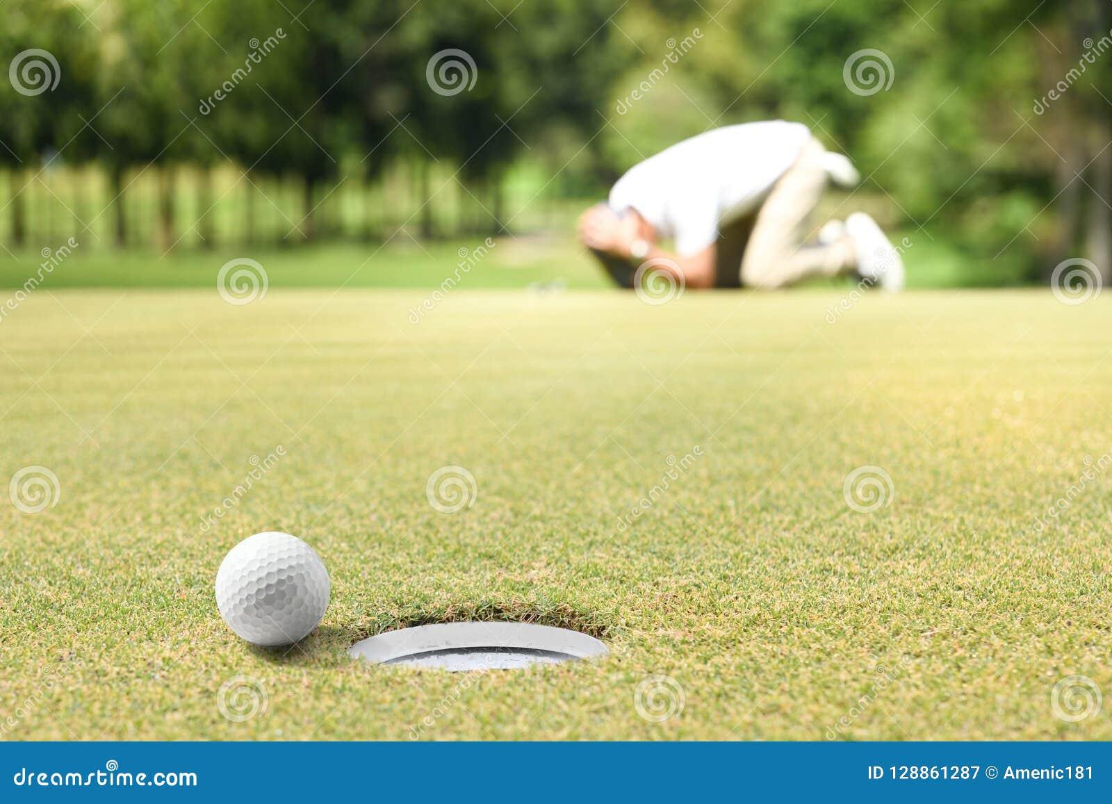 Il giocatore di golf dell uomo che ritiene deludente dopo una palla da golf messa ha mancato il foro