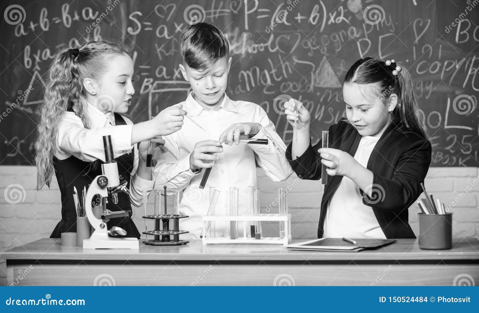 Il giorno dei bambini chimica Di nuovo al banco studenti che fanno gli esperimenti di biologia con il microscopio Apprendimento d