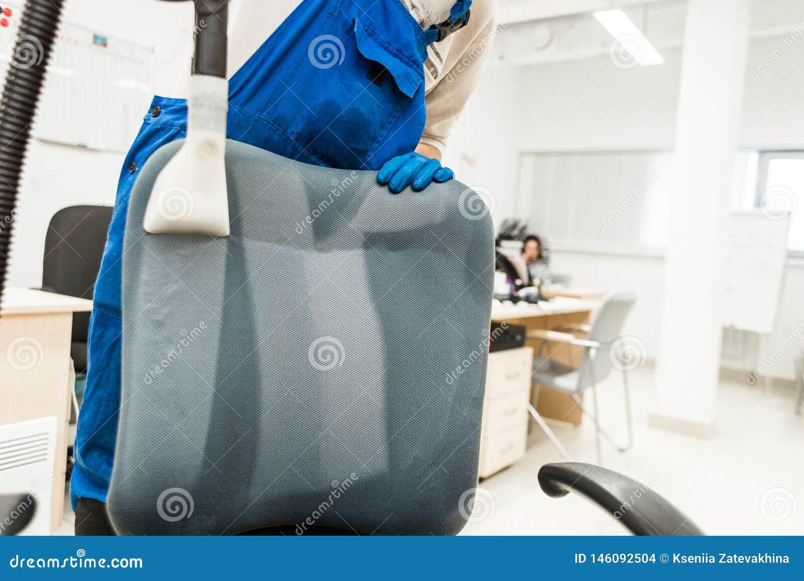 Il giovane in abiti da lavoro ed in guanti di gomma pulisce la sedia dell ufficio con attrezzatura professionale
