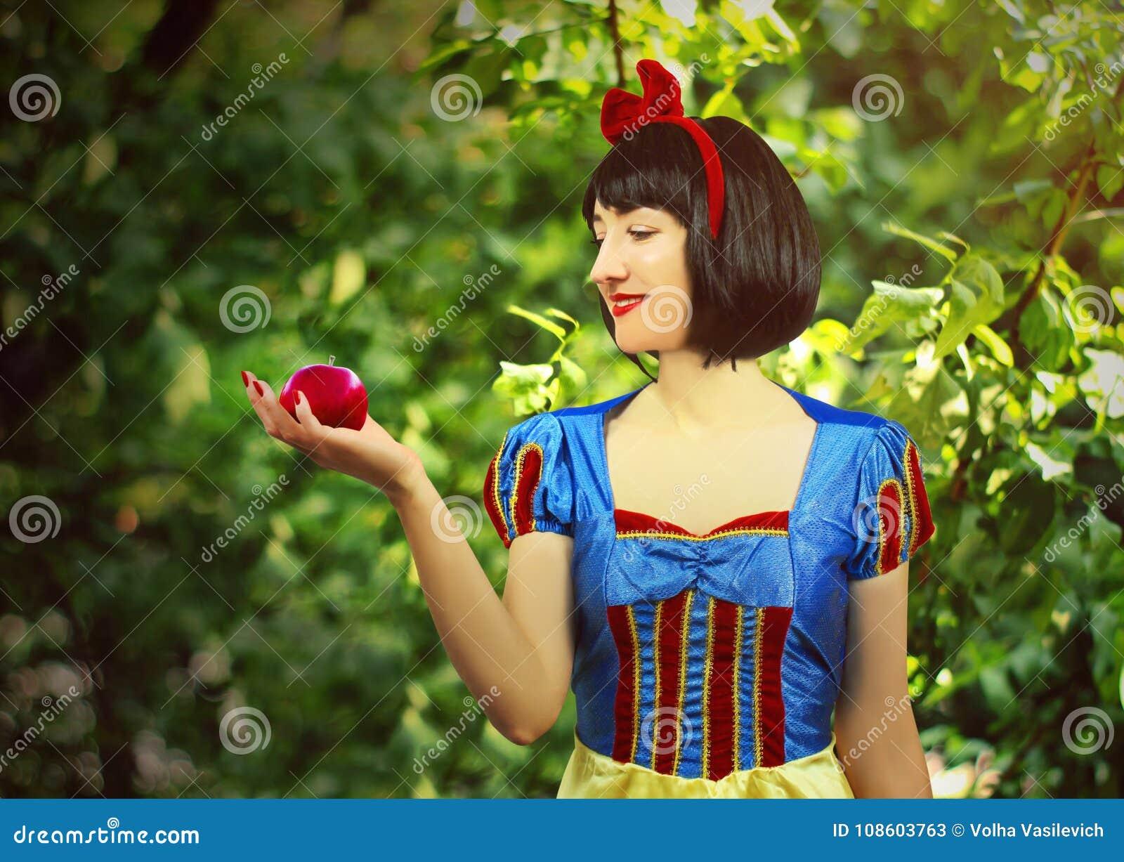 Il giovane bello primo piano bianco come la neve tiene una mela avvelenata rosso contro lo sfondo degli alberi nella foresta