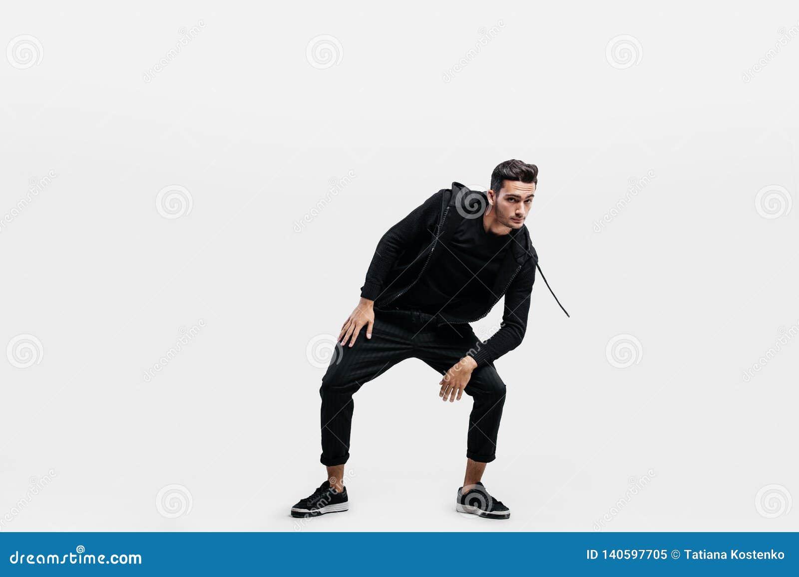 Il giovane bello vestito in vestiti del nero di sport sta ballando il ballo della via