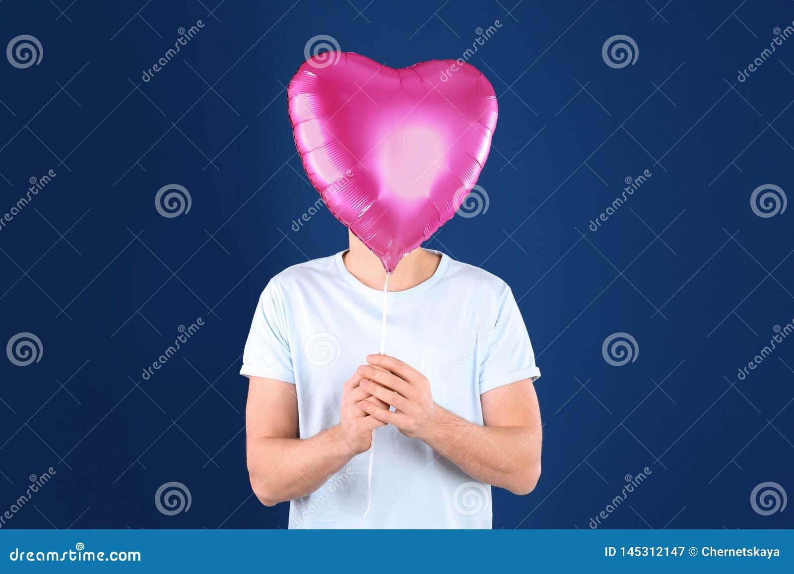Il giovane con cuore ha modellato il pallone su fondo blu